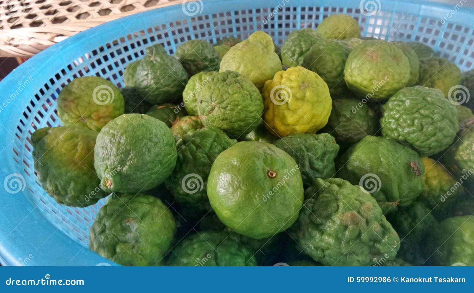Vers groen en geel bergamotfruit in blauwe mand in de keuken stock ...