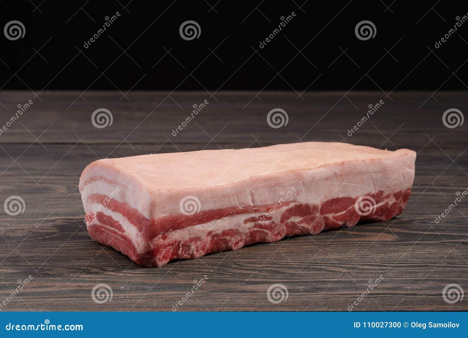 Vers ruw geheel rek van varkensvleeslendestuk met ribben en vet op een donkere achtergrond