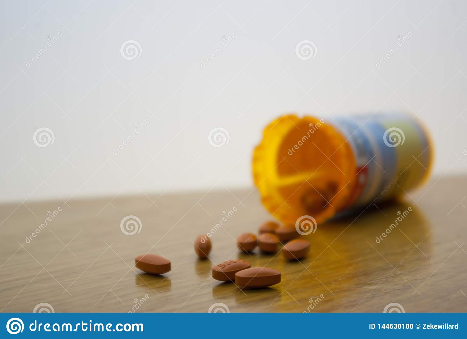 Verschüttete orange Pillen auf weißer Oberfläche