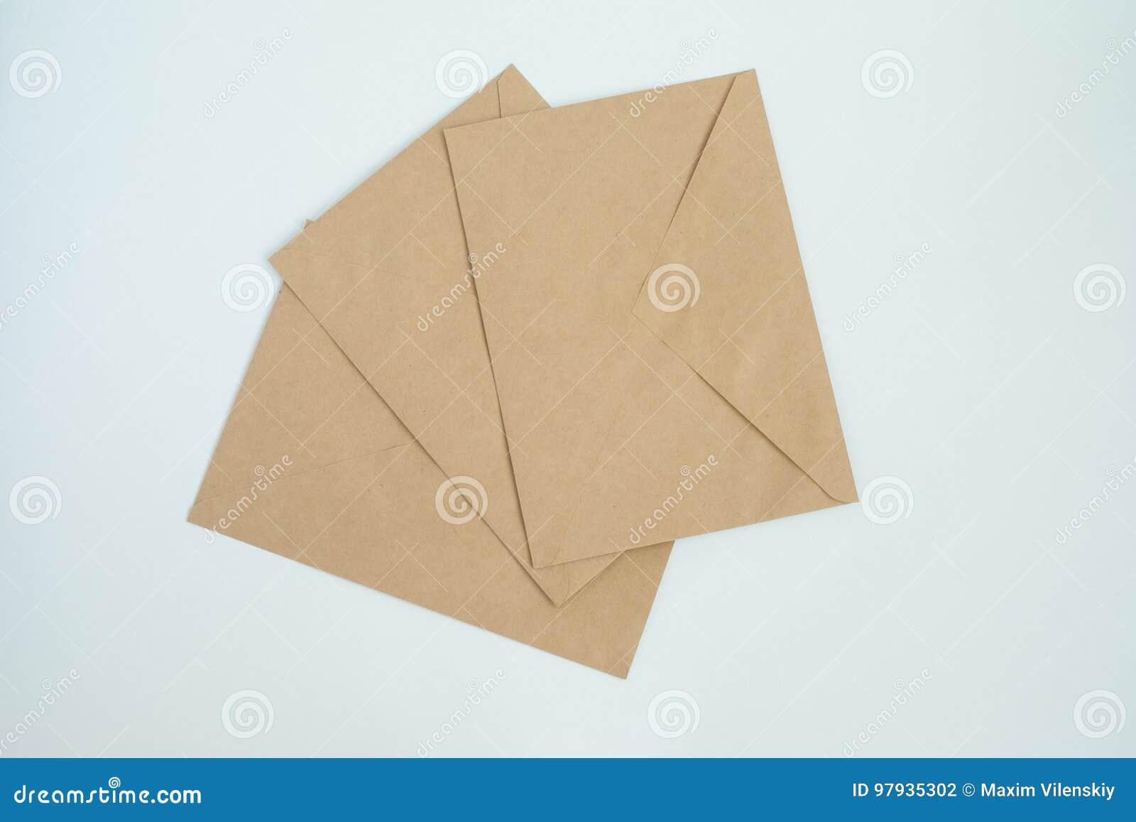 Verscheidene enveloppen van bruin brievendocument, op wit close-up als achtergrond, hoogste mening