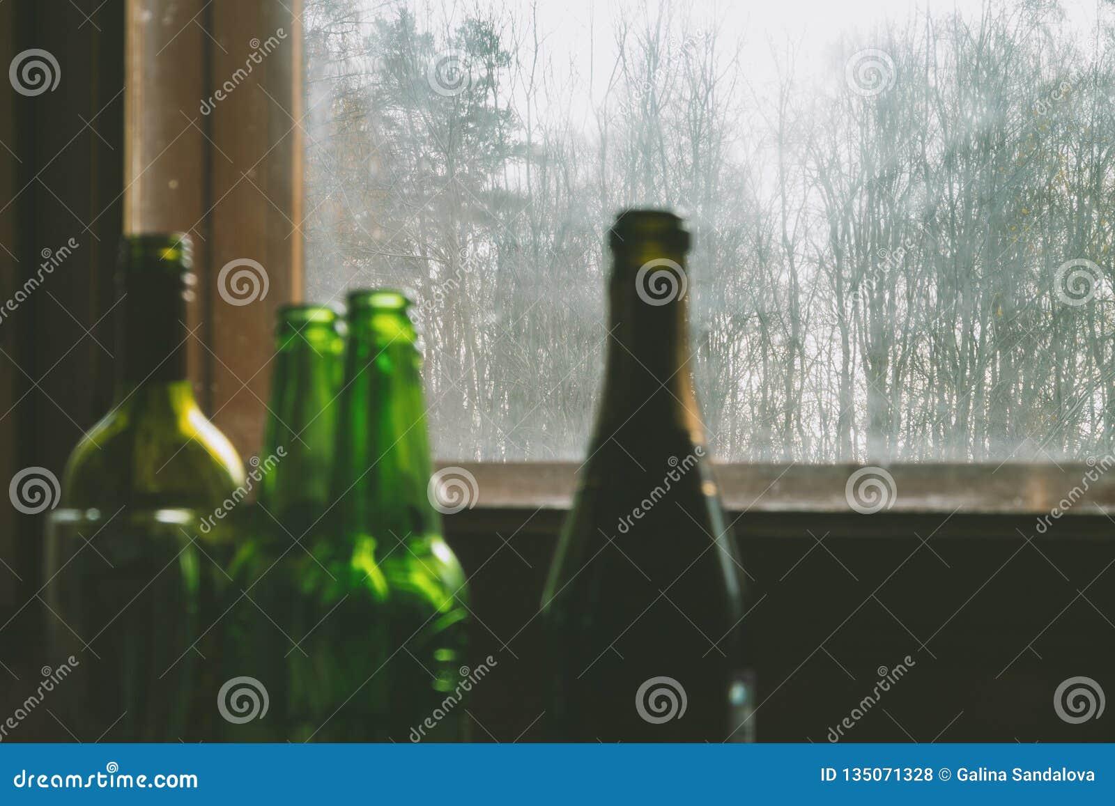 Verscheidene lege flessen alcohol dichtbij het vuile venster Selectieve nadruk Alcoholisme, dronkenschap, eenzaamheid en depressi