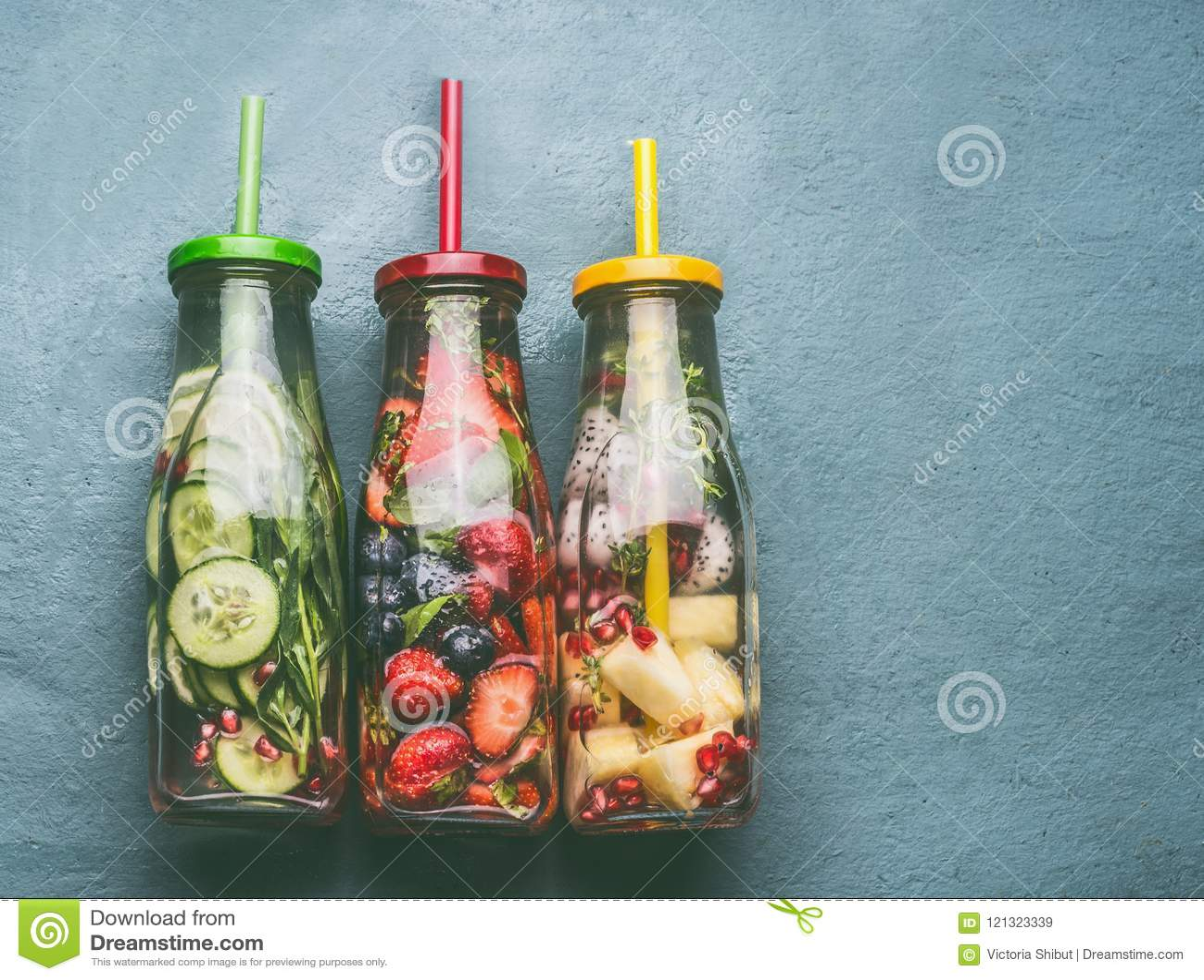 Verscheidenheid van kleurrijk gegoten water in flessen met vruchten bessen, komkommer, kruiden en drankstro op grijze achtergrond