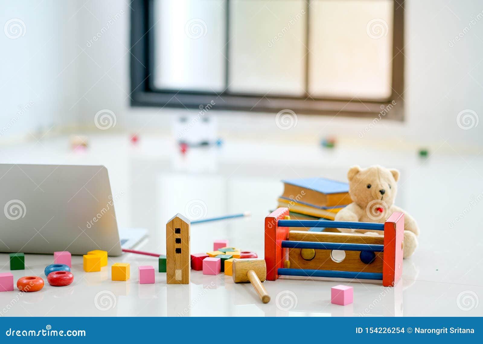 Verschiedene Arten von Spielwaren und von Puppe werden auf den Boden nahe zur Laptop-Computer vor Glasfenstern gesetzt