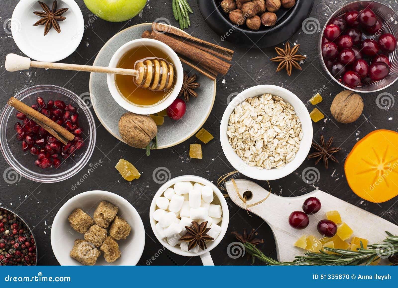 Verschiedene Bestandteile für Wintersaisonbacken und andere Rezepte, Granatapfel, Honig, orezhi, Äpfel, Persimonen, Kräuter