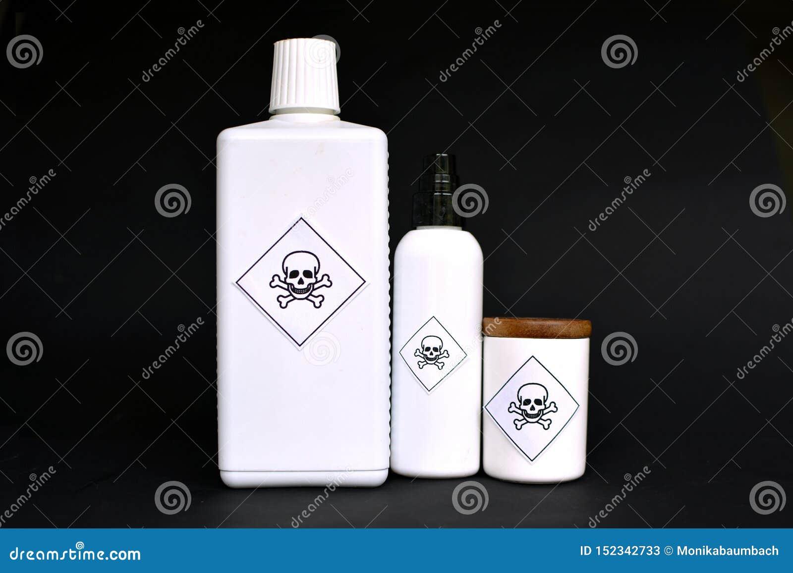 Verschiedene geformte weiße Behälter mit Giftaufklebern auf schwarzem Hintergrund