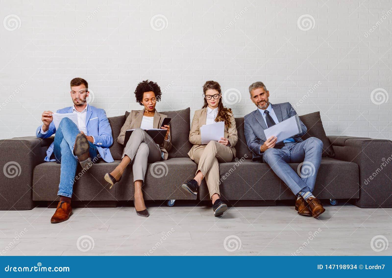 Verschiedene Geschäftsleute, die auf ein Interview warten