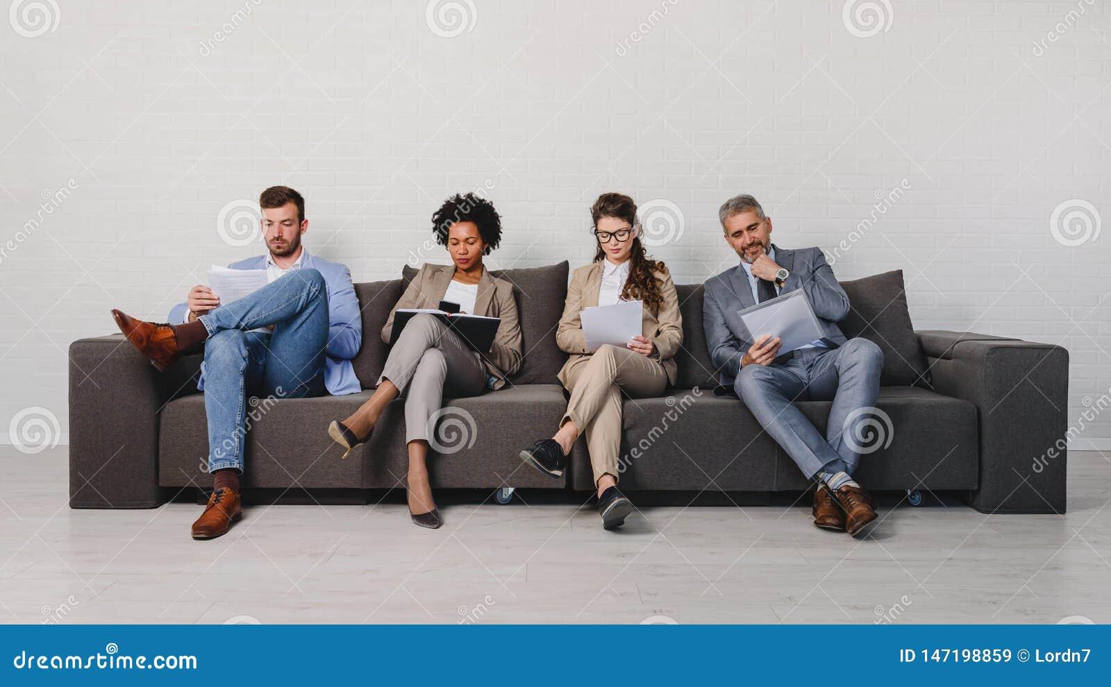 Verschiedene Geschäftsleute, die auf eine Verabredung warten