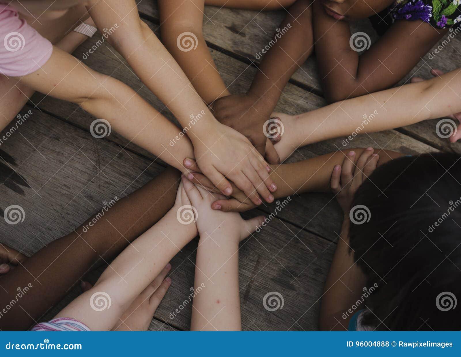 Verschiedene Hände sind verbinden zusammen auf dem Holztisch