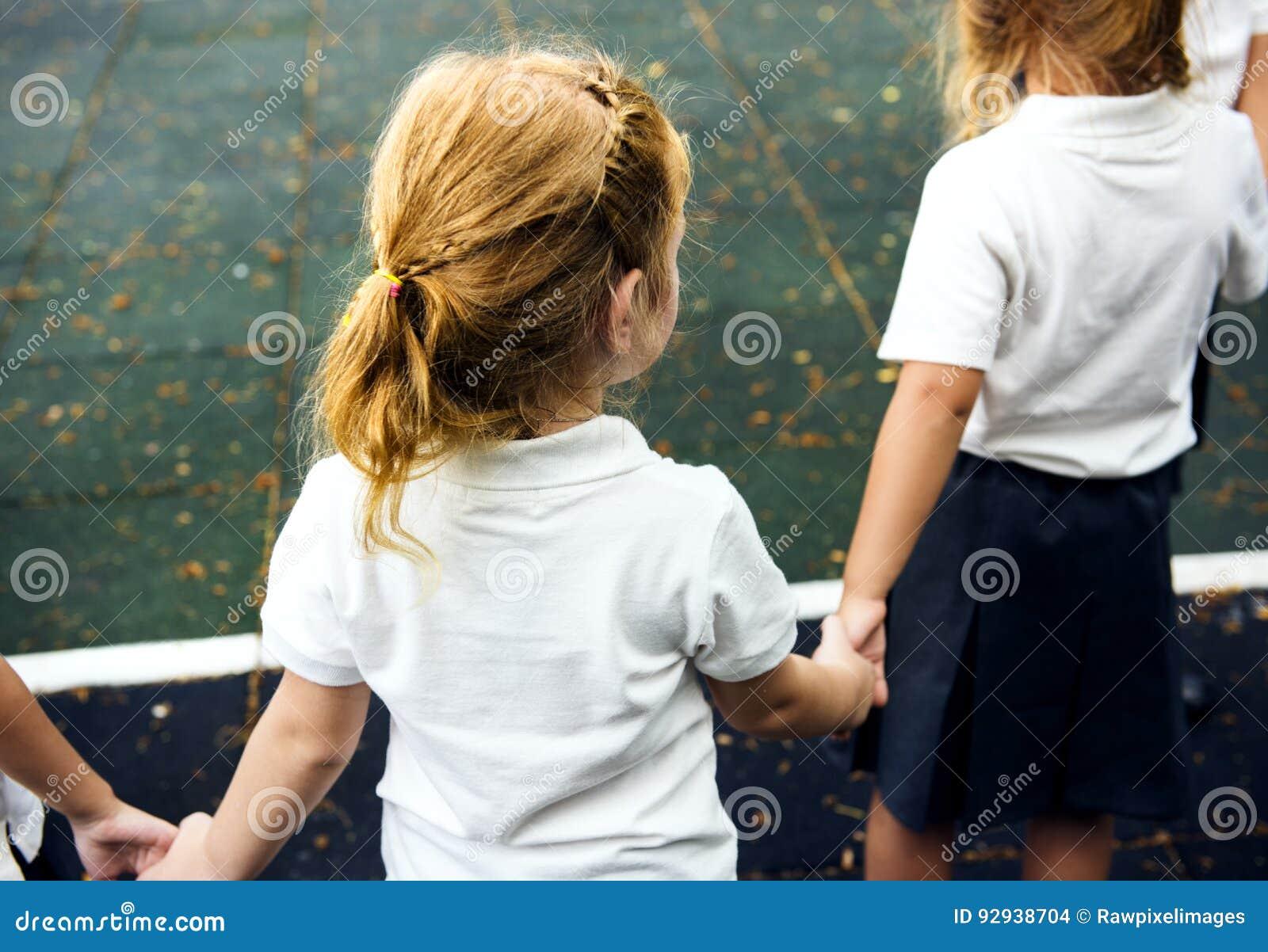 Verschiedene Kindergartenstudenten, die zusammen Händchenhalten stehen