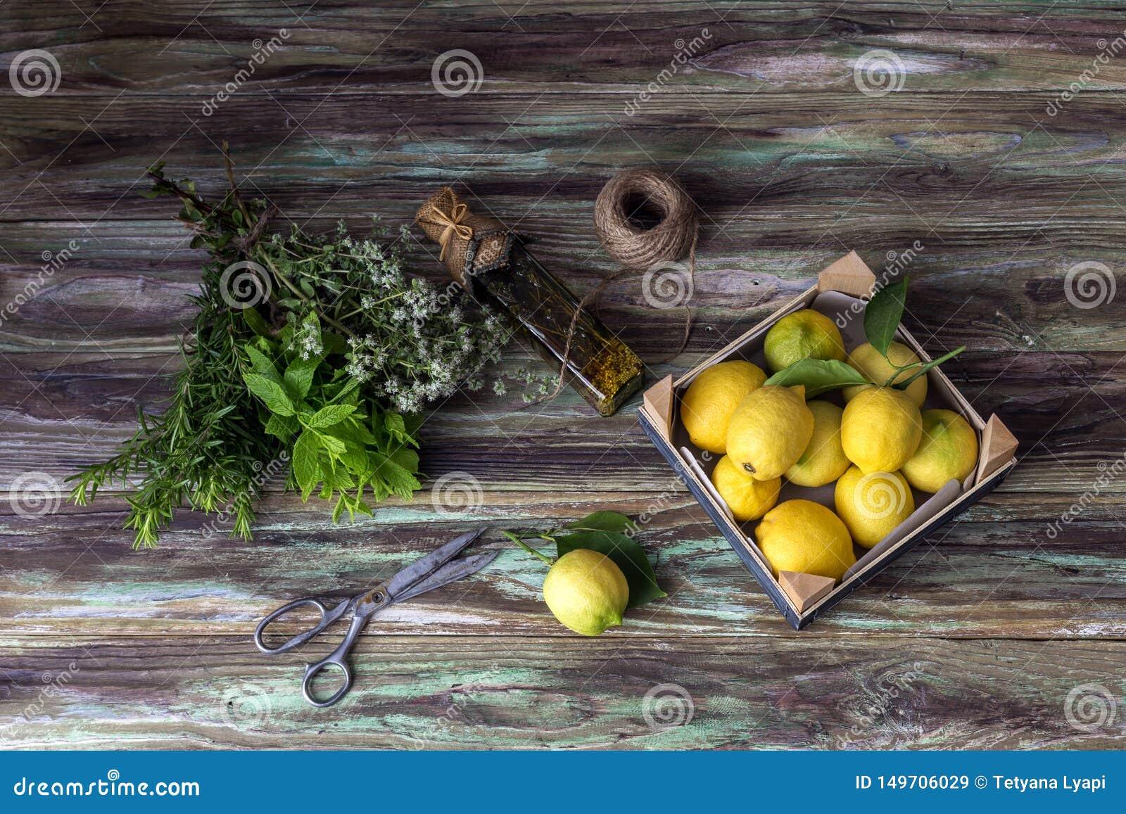 Verschiedene Kräuter, Gewürze, Zitronen und Olivenöl auf einem hölzernen Hintergrund