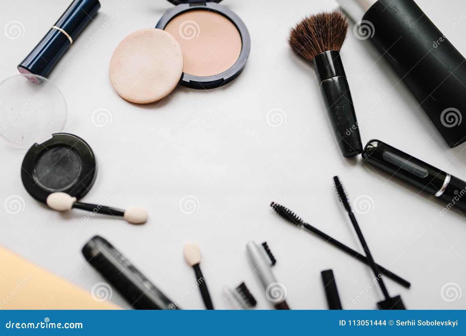 Verschiedene Satzkosmetische Produkte: Bürsten, Lidschatten, Pulver, Wimperntusche, Kosmetik lokalisiert auf hellem weißem Hinter