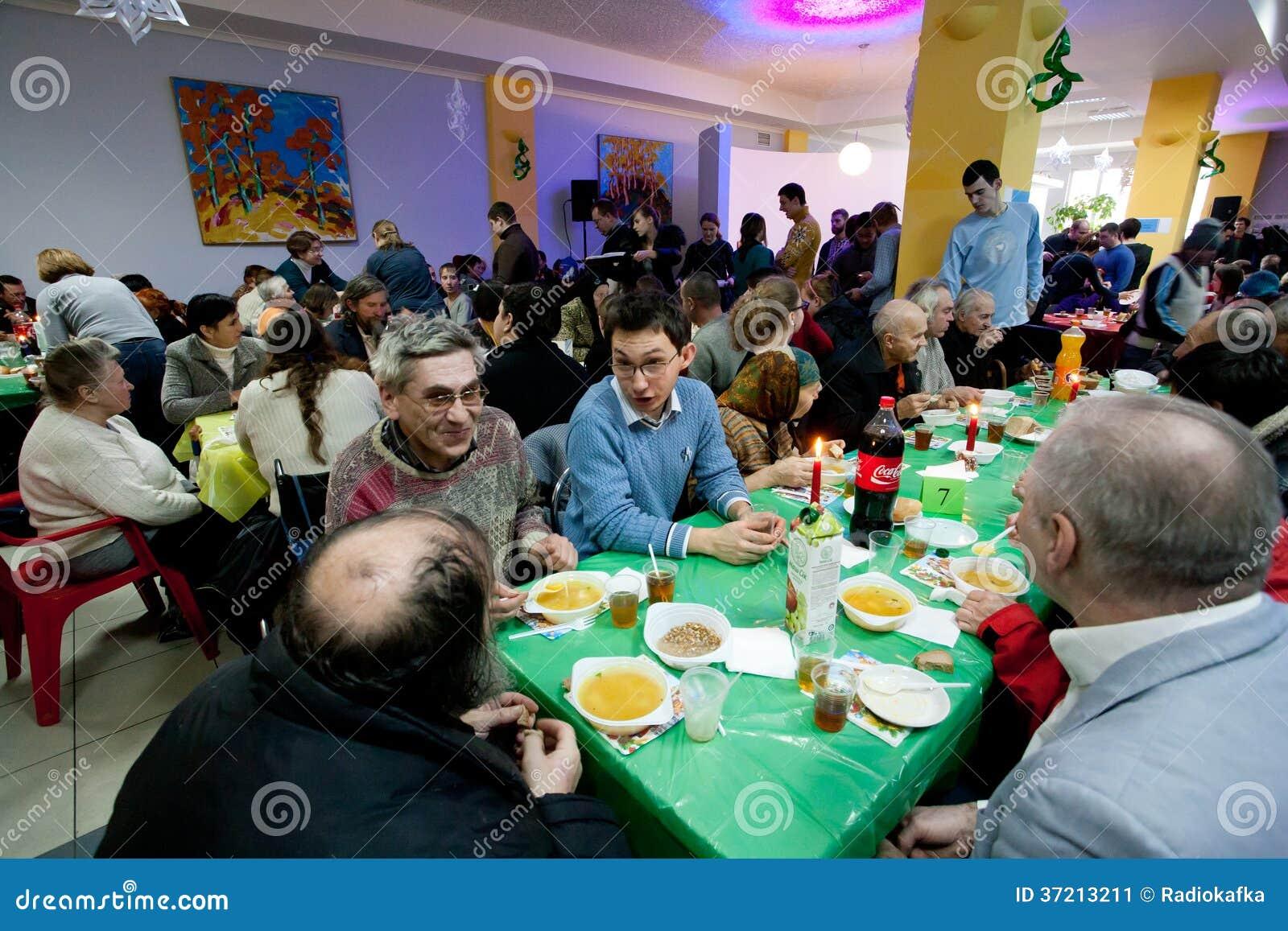 Verschillende mensen die bij de lijsten bij het diner van de Kerstmisliefdadigheid voor de daklozen spreken