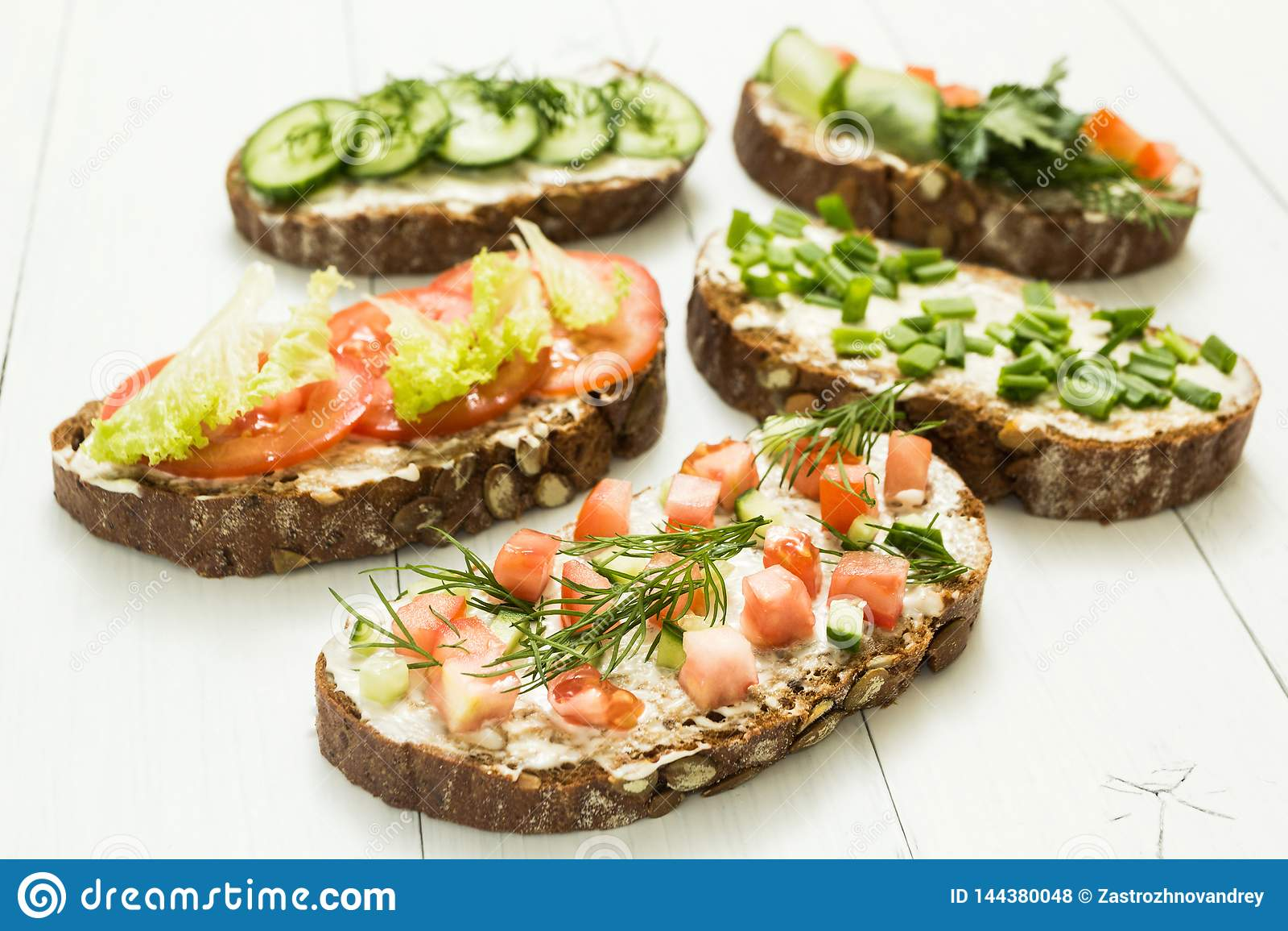 Verschillende soorten kleurrijke sandwiches op witte houten achtergrond