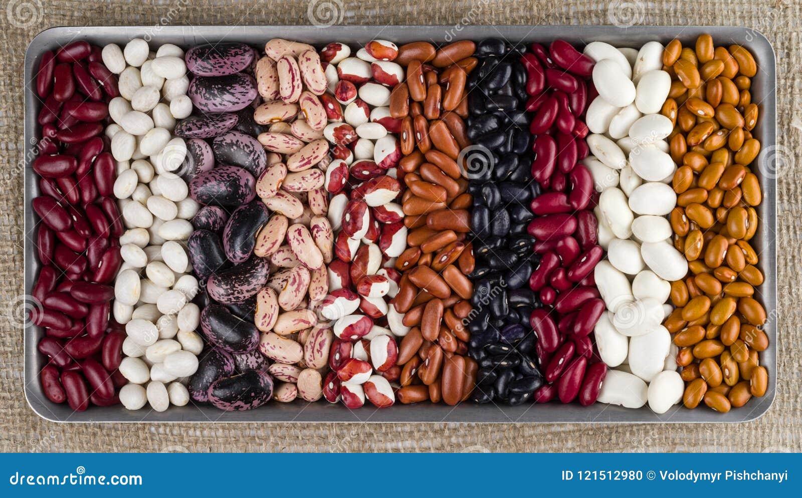 Verschillende verscheidenheden van nierbonen tegen de achtergrond van de ruwe textuur van jute