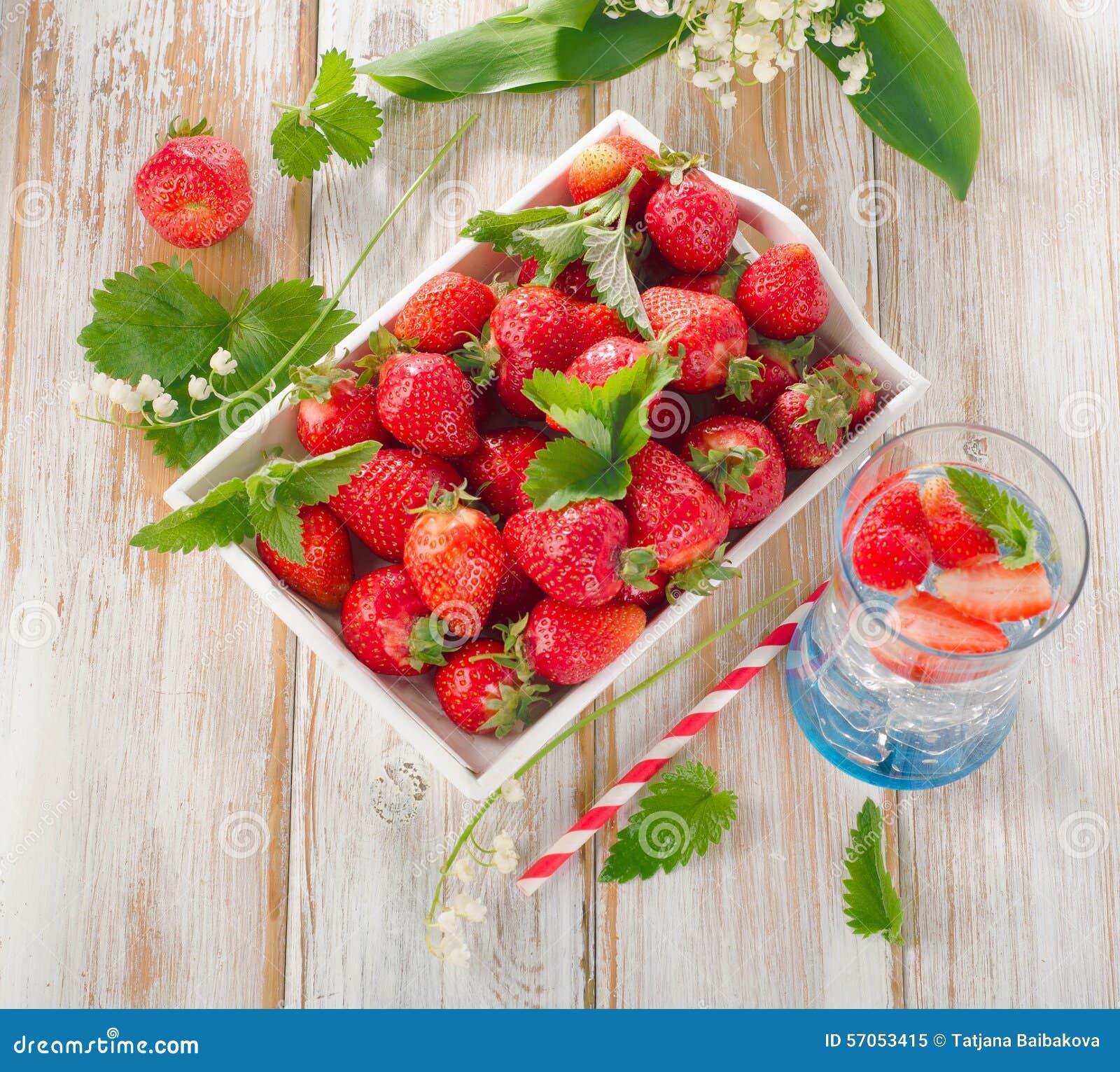 Verse aardbeien en koud water op een houten lijst