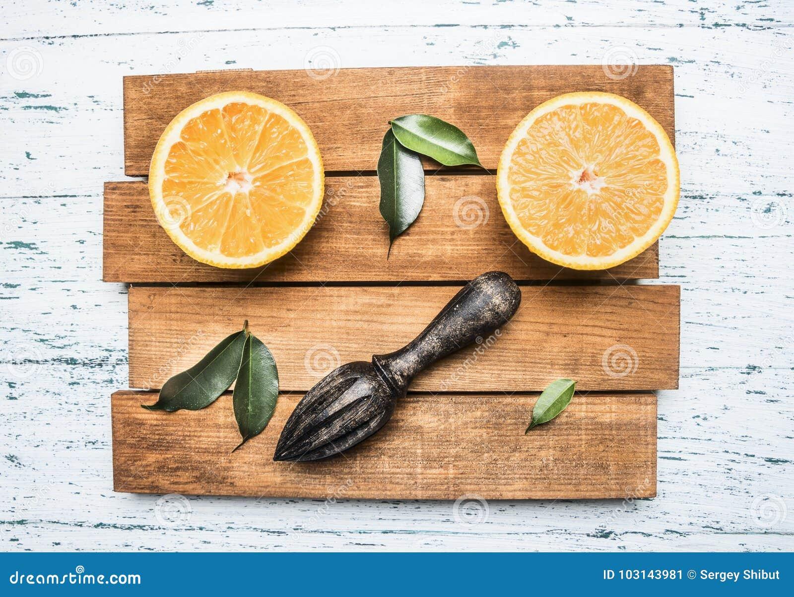 Verse besnoeiingssinaasappelen met bladeren en een houten verbrijzeling voor fruit, op rustiek houten dienblad, hoogste mening