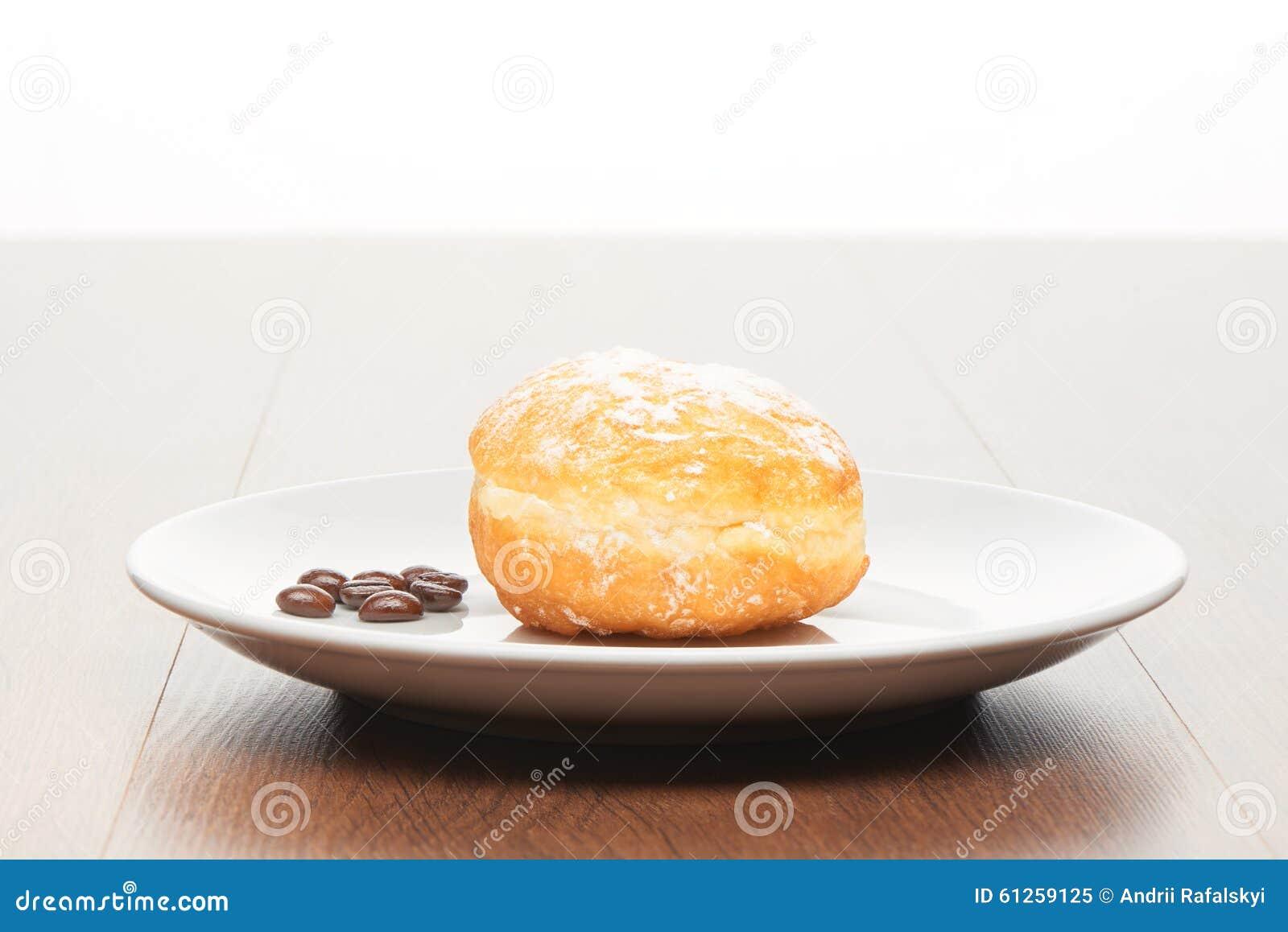 Verse doughnut met suikerglazuursuiker en koffiebonen op witte ceramische plaat op heldere lichtbruine houten lijst