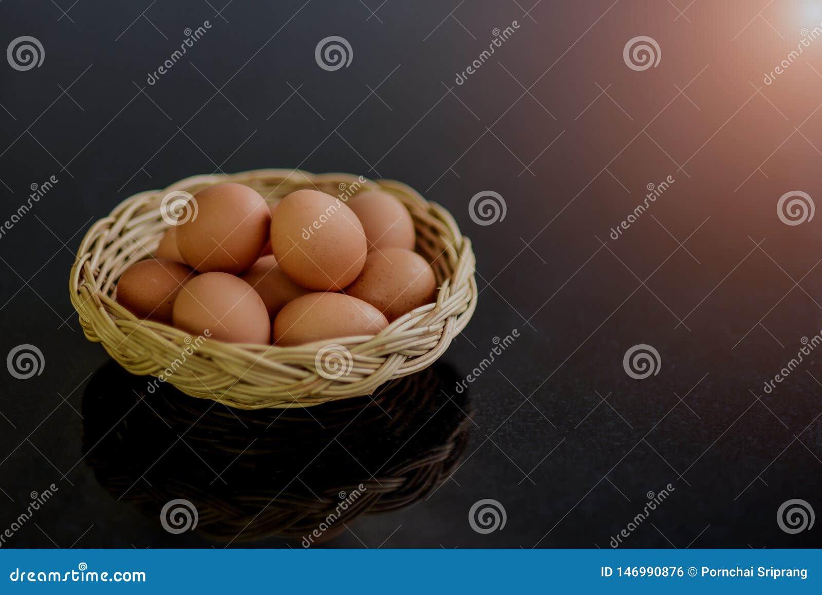 Verse eieren in vele rieten manden op een zwarte die steenlijst als grondstof voor het koken wordt voorbereid
