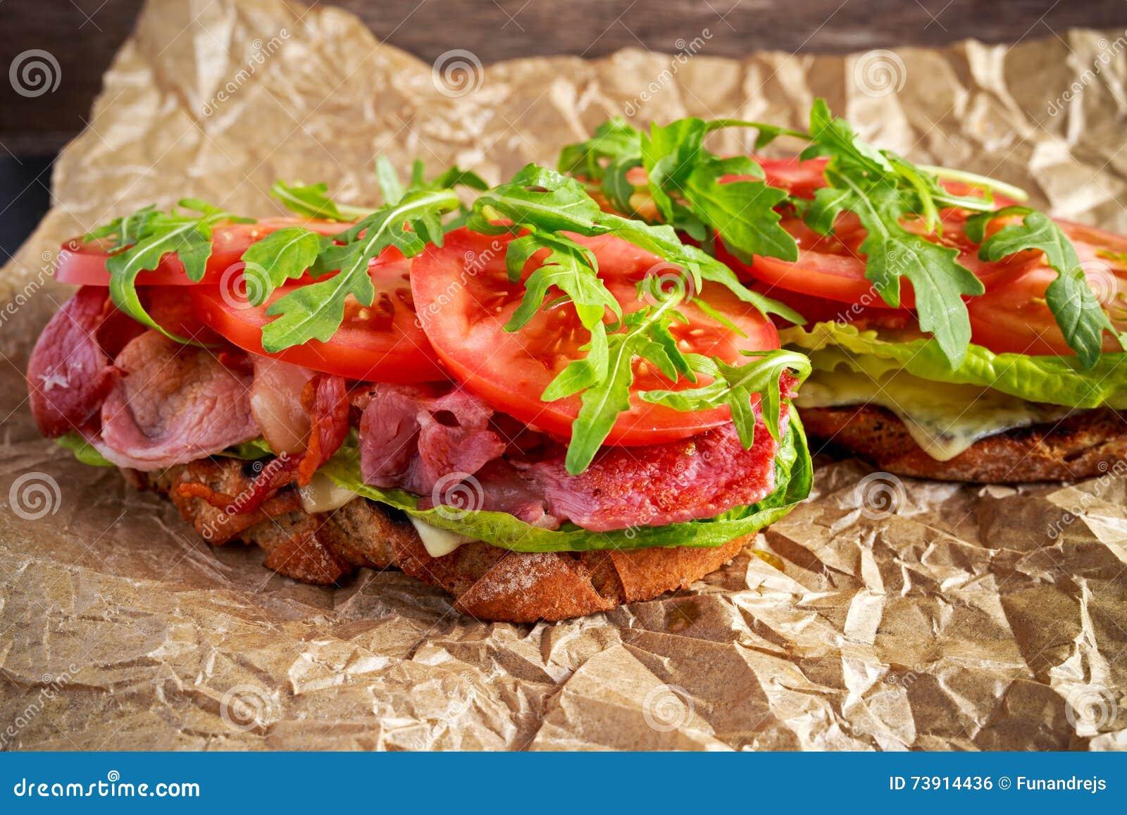 Verse eigengemaakte BLT-sandwich op geroosterd brood met bacon, sla, rundvleestomaat, rode uien, wilde raket en spaanders