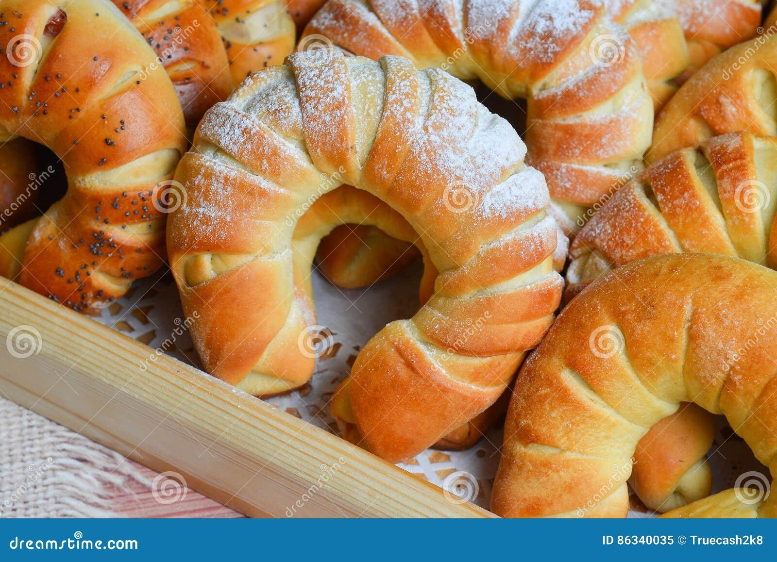Verse enkel gebakken zoete broodjes of broodjes op dienblad voor ontbijt en thee of koffietijd op houten achtergrond