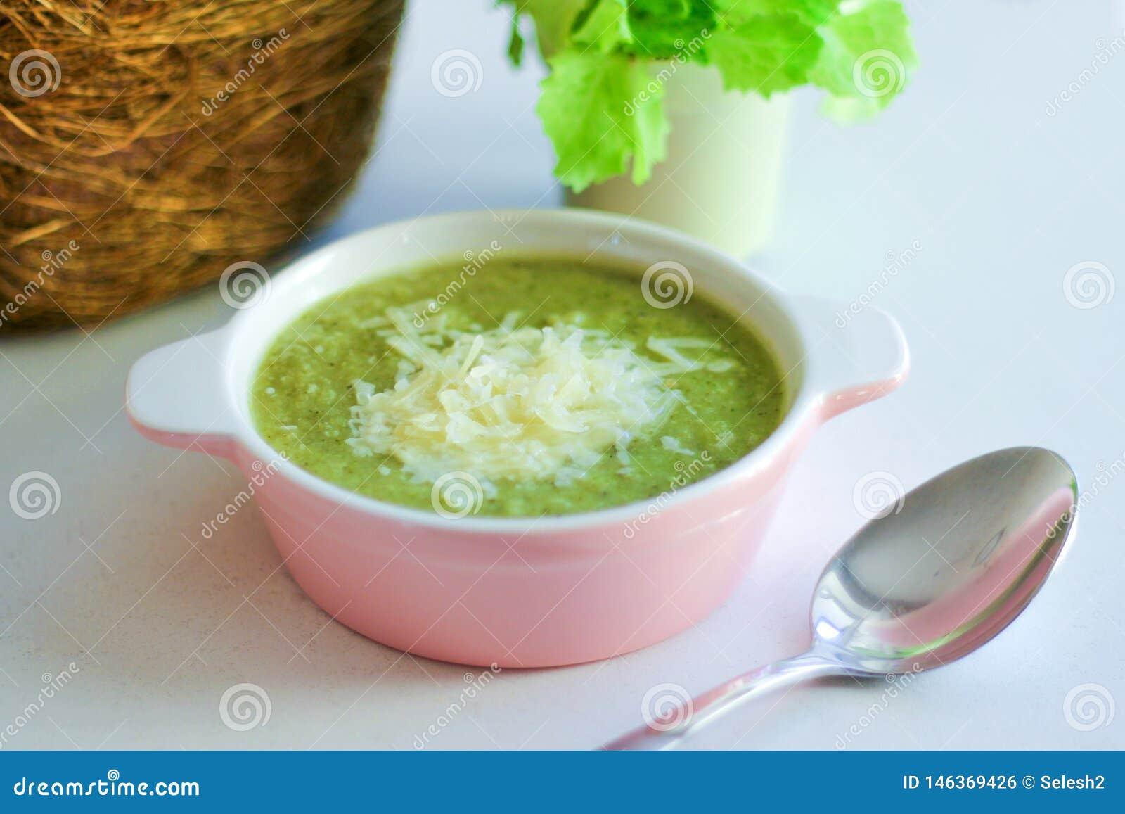 Verse fijngestampte soep met broccoli en geraspte Parmezaanse kaas in een roze plaat op een lichte achtergrond