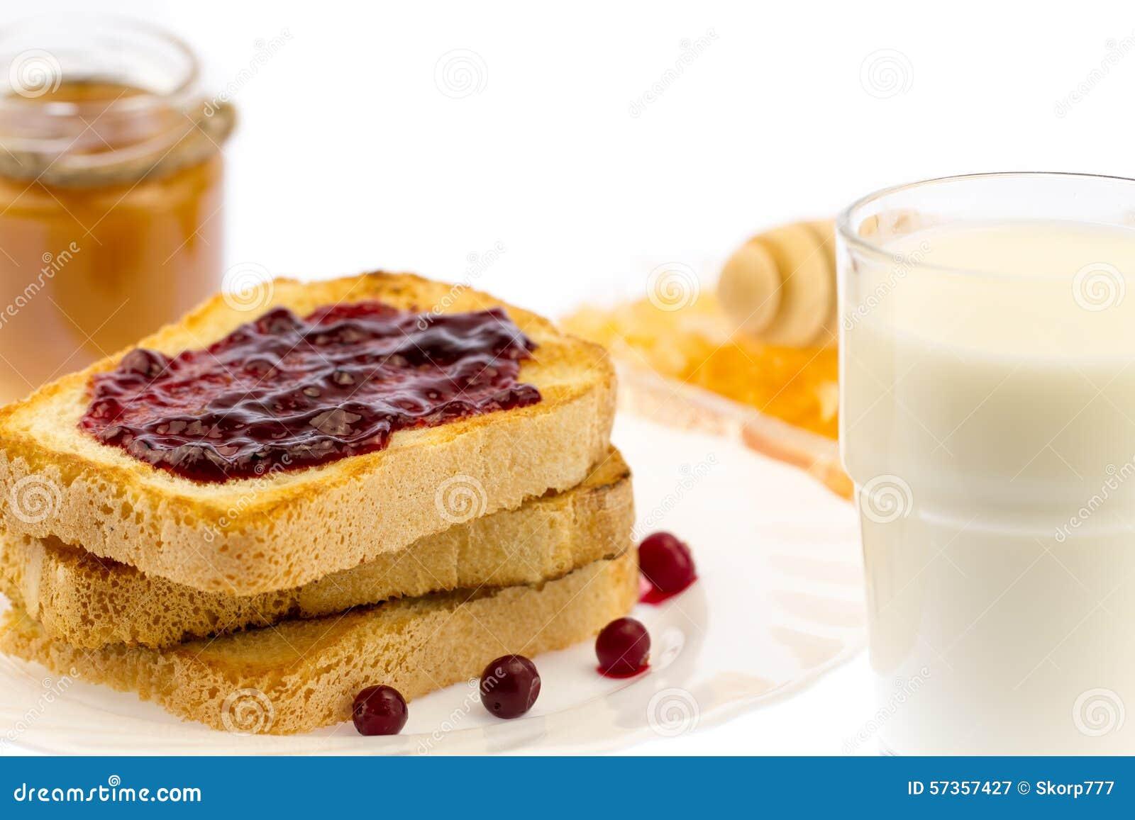 Verse Franse toost met honing en jam op een witte plaat met bessen op een witte achtergrond