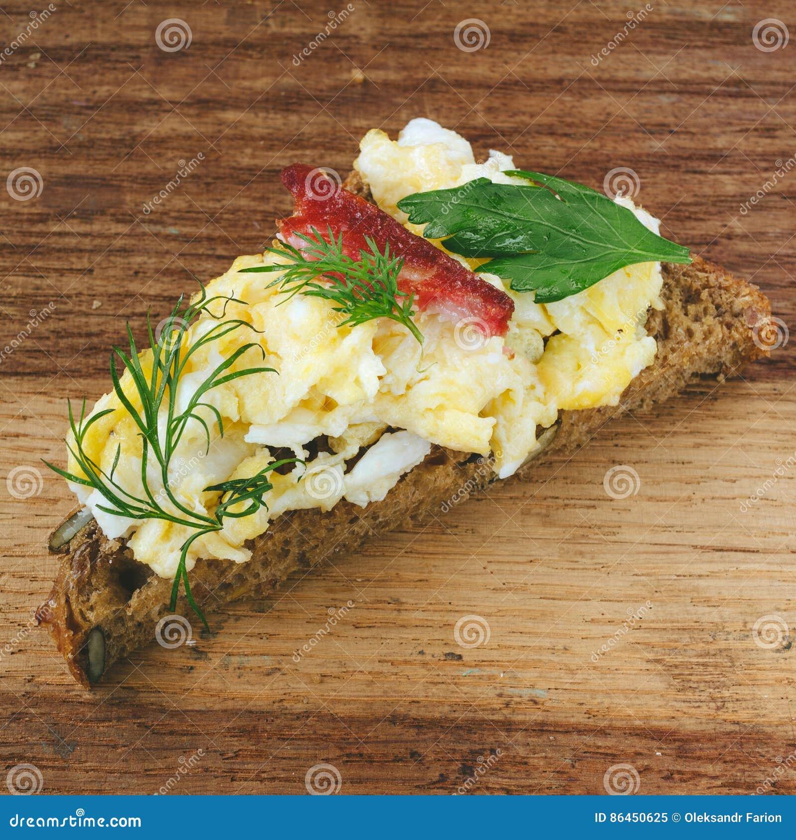 Verse gekookte roereieren met worst en kruiden op stuk van brood, houten achtergrond