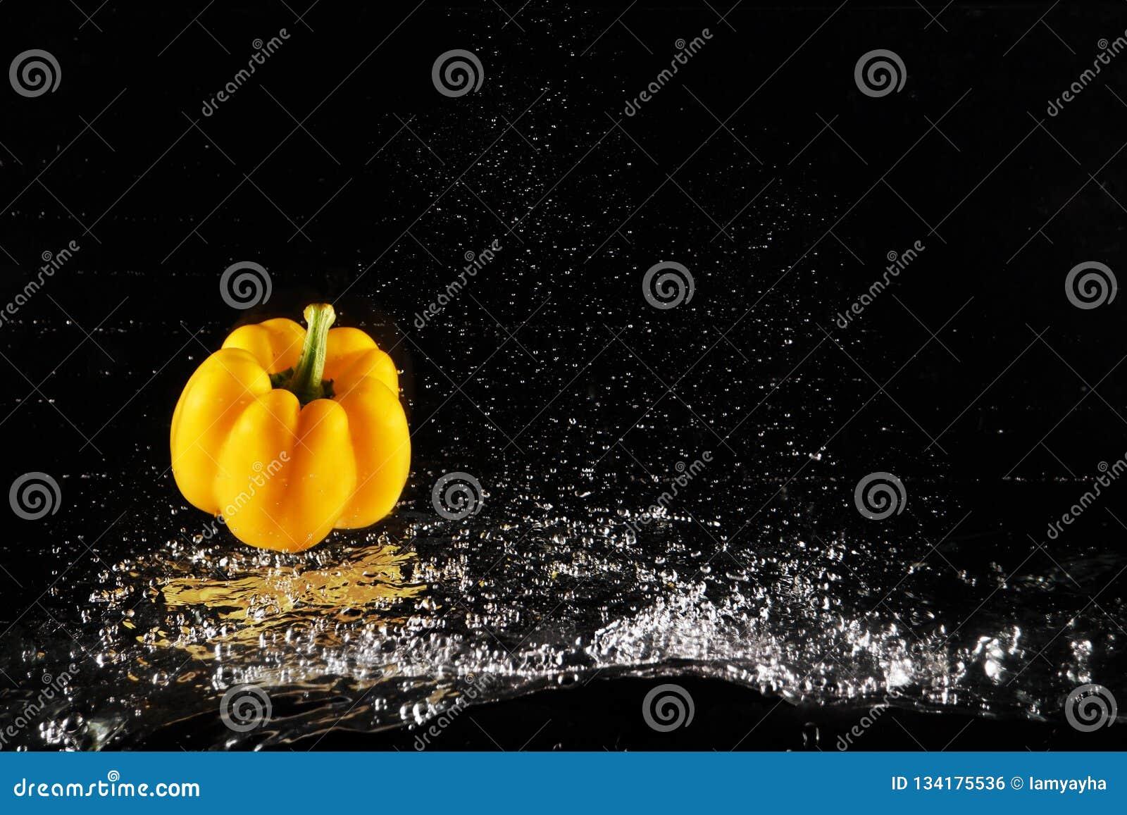 Verse Gele Groene paprika met Waterplons en Geïsoleerde Bel De ruimte van het exemplaar Sappige Gele Paprika Dropped in Water op