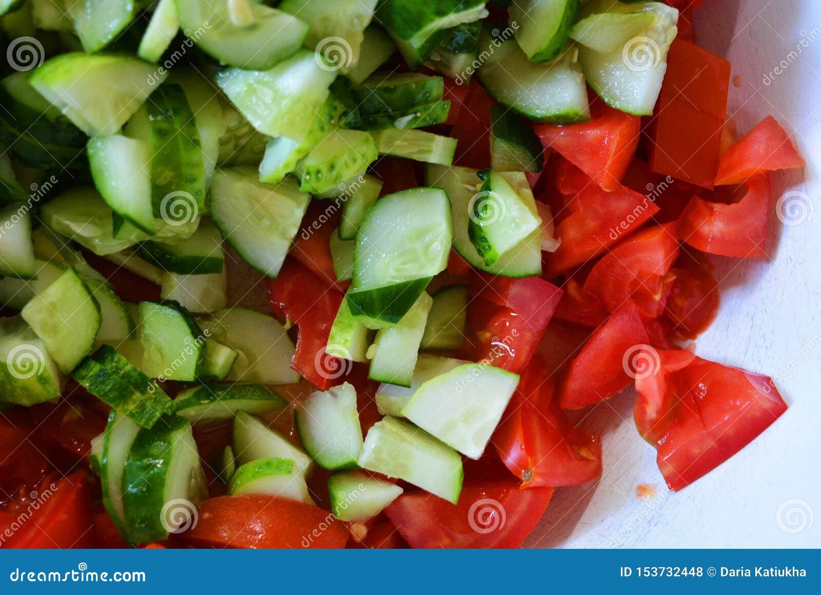 Verse gezonde groenten, kleine plakken van groene komkommers en rode tomaten voor de zomersalade, ingrediënten voor salade