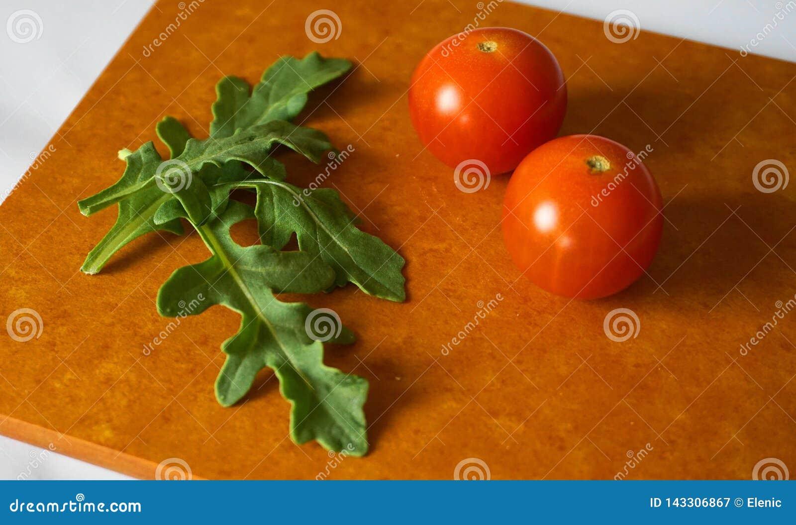 Verse groene arugulabladeren en kersentomaten op houtvezelplaat