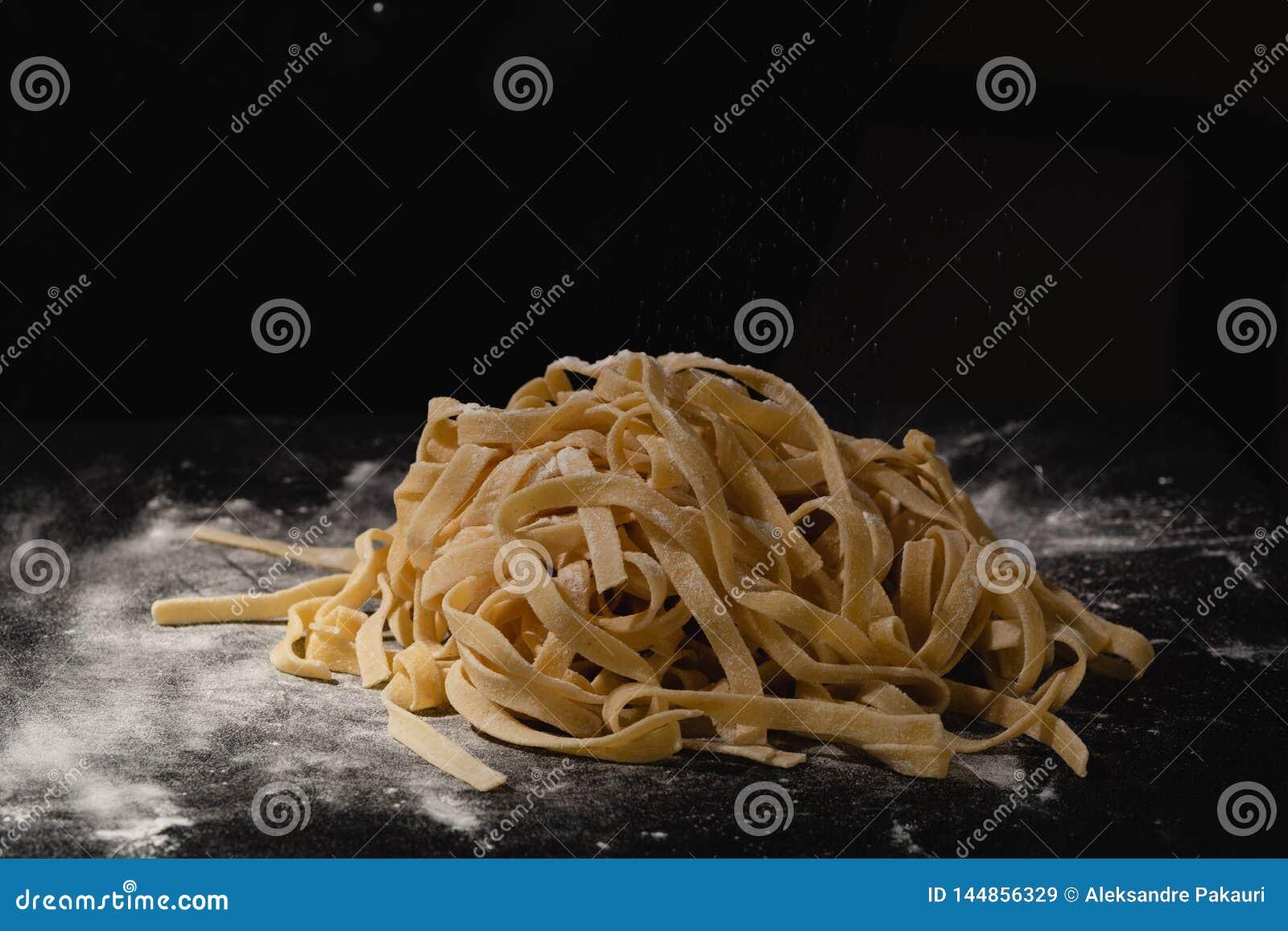 Verse Italiaanse ongekookte eigengemaakte deegwaren Handen die deegwaren maken spaghetti Verse Italiaanse spaghetti Close-up van