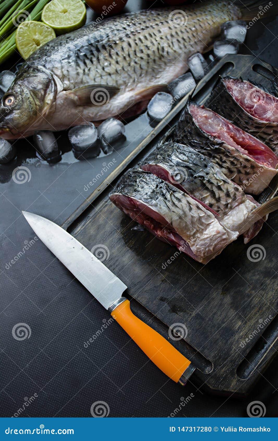 Verse karper op een donkere achtergrond met greens en groenten Besnoeiing in stukkenkarper op een houten raad