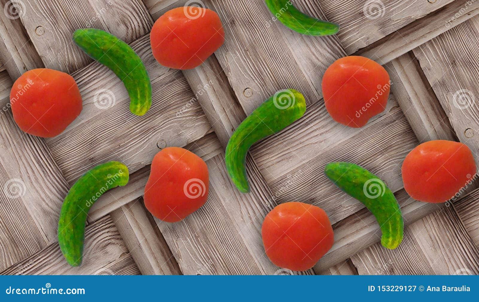 Verse lelijk croocked groene komkommers en verse rode tomaten op houten achtergrond