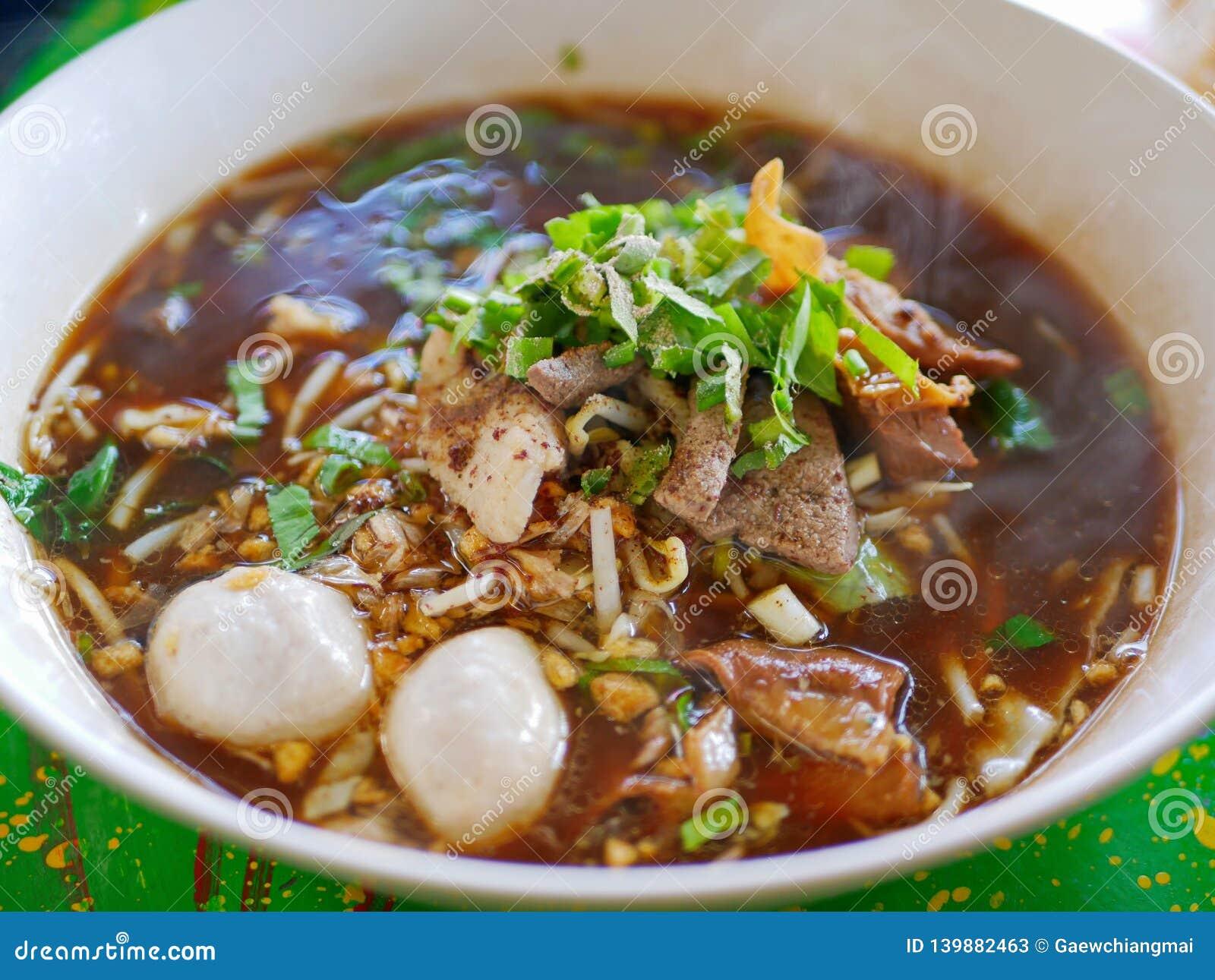 Verse noedelssoep met varkensvlees en zijn smakelijke dikke bouillon Guay Tiao Nam Tok Moo - heerlijk en gezond straatvoedsel in