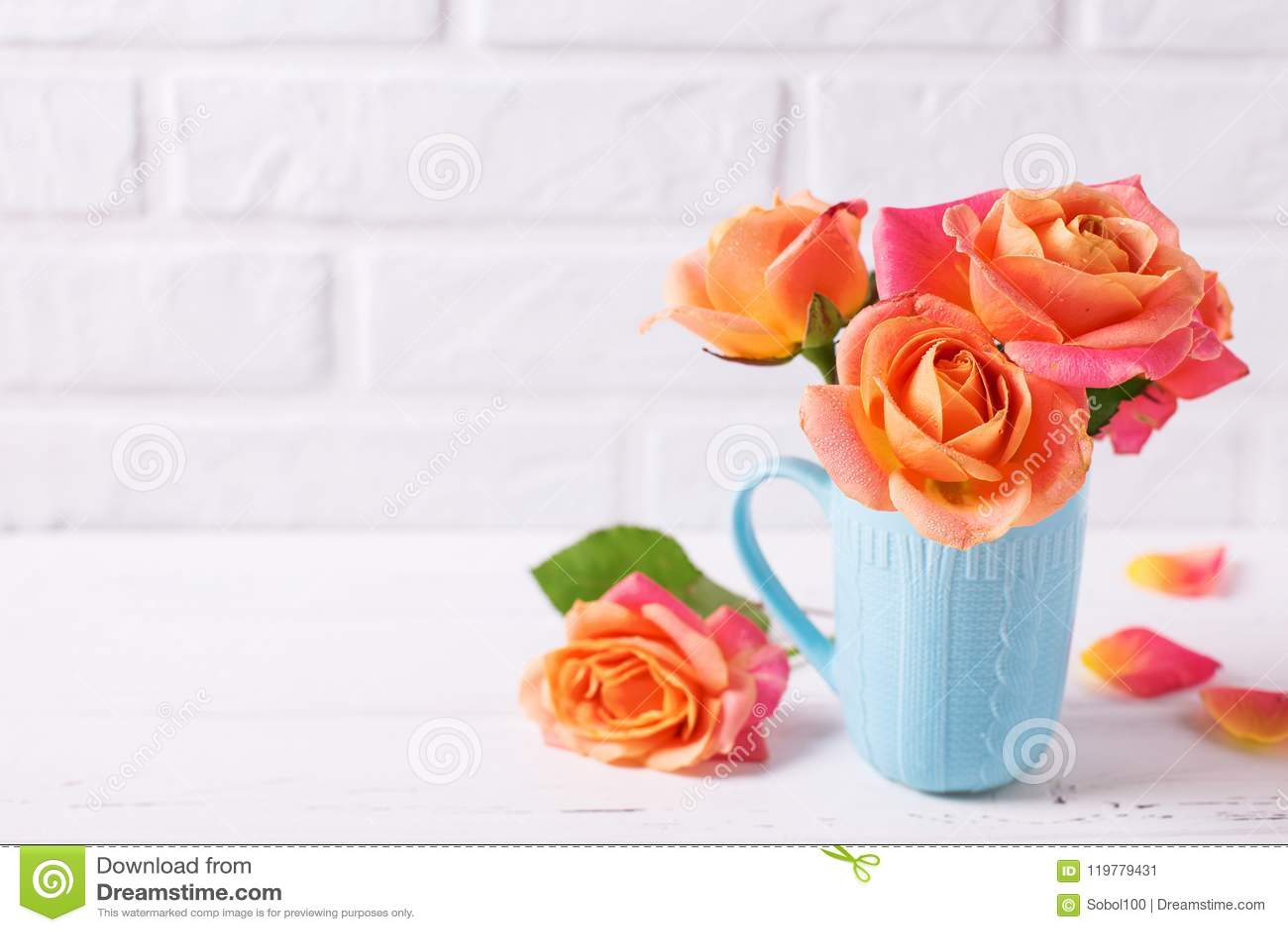 Verse oranje rozen in blauwe kop op witte houten achtergrond agains
