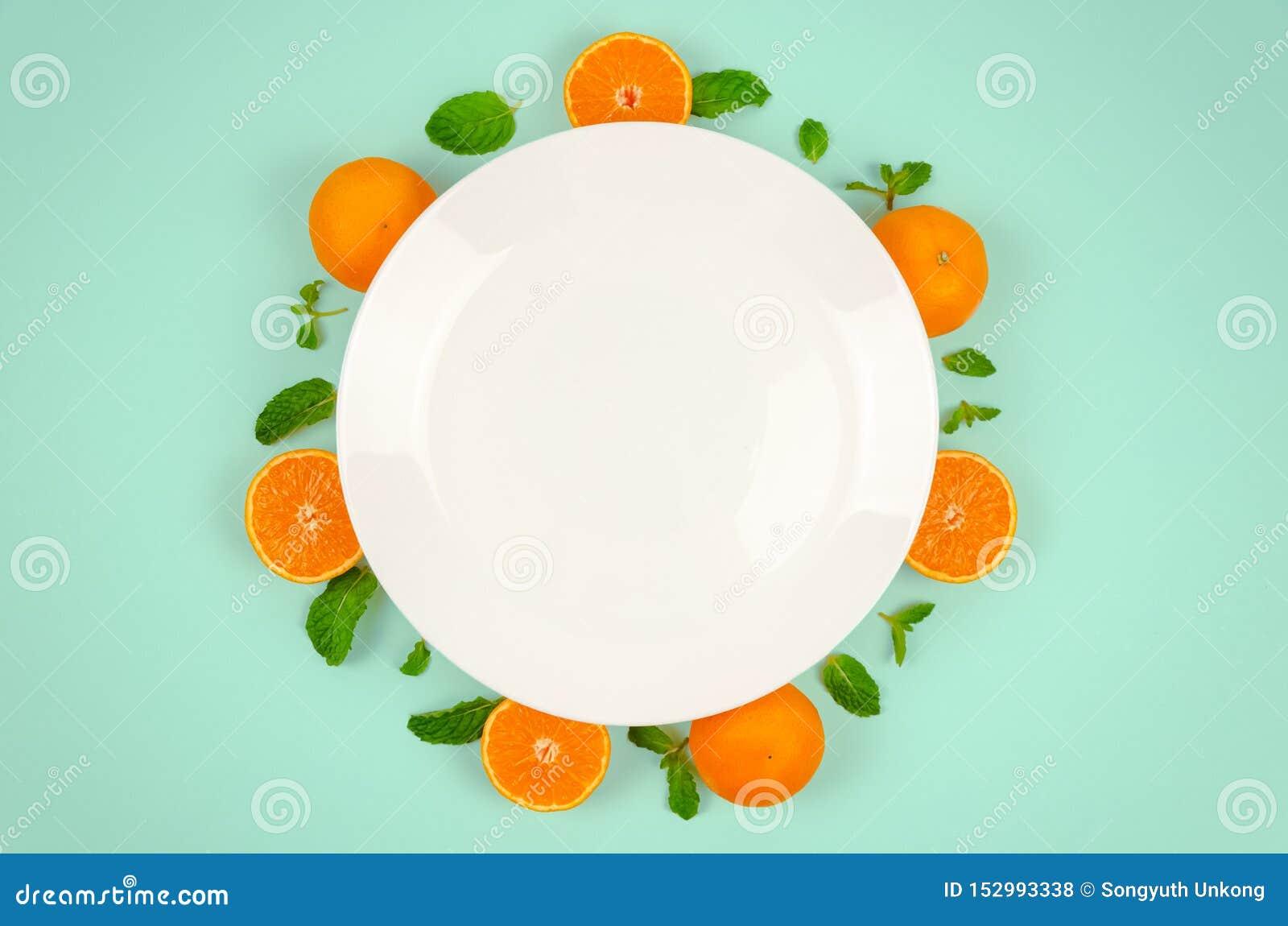 Verse oranje vruchten en muntbladeren op hoogste mening met witte plaat en pastelkleur groene kleurenachtergrond voor gezond voed