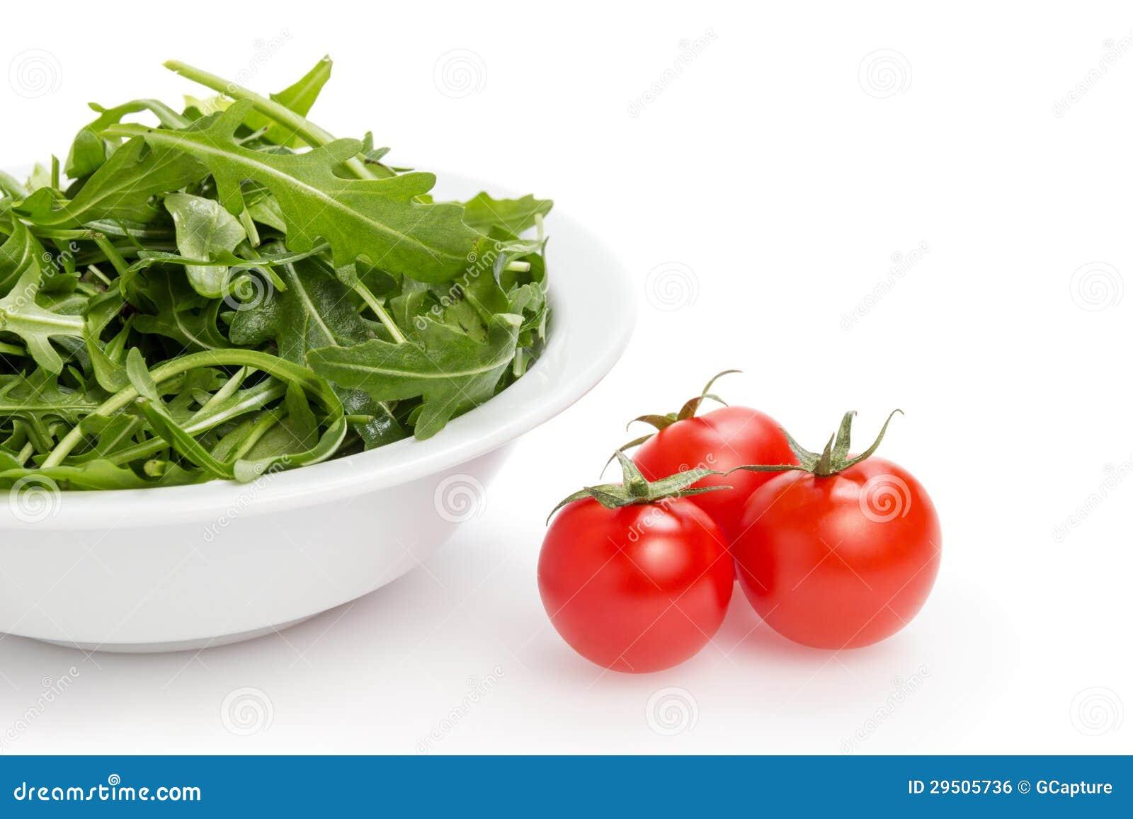 Verse rucolabladeren in een kom en tomaten