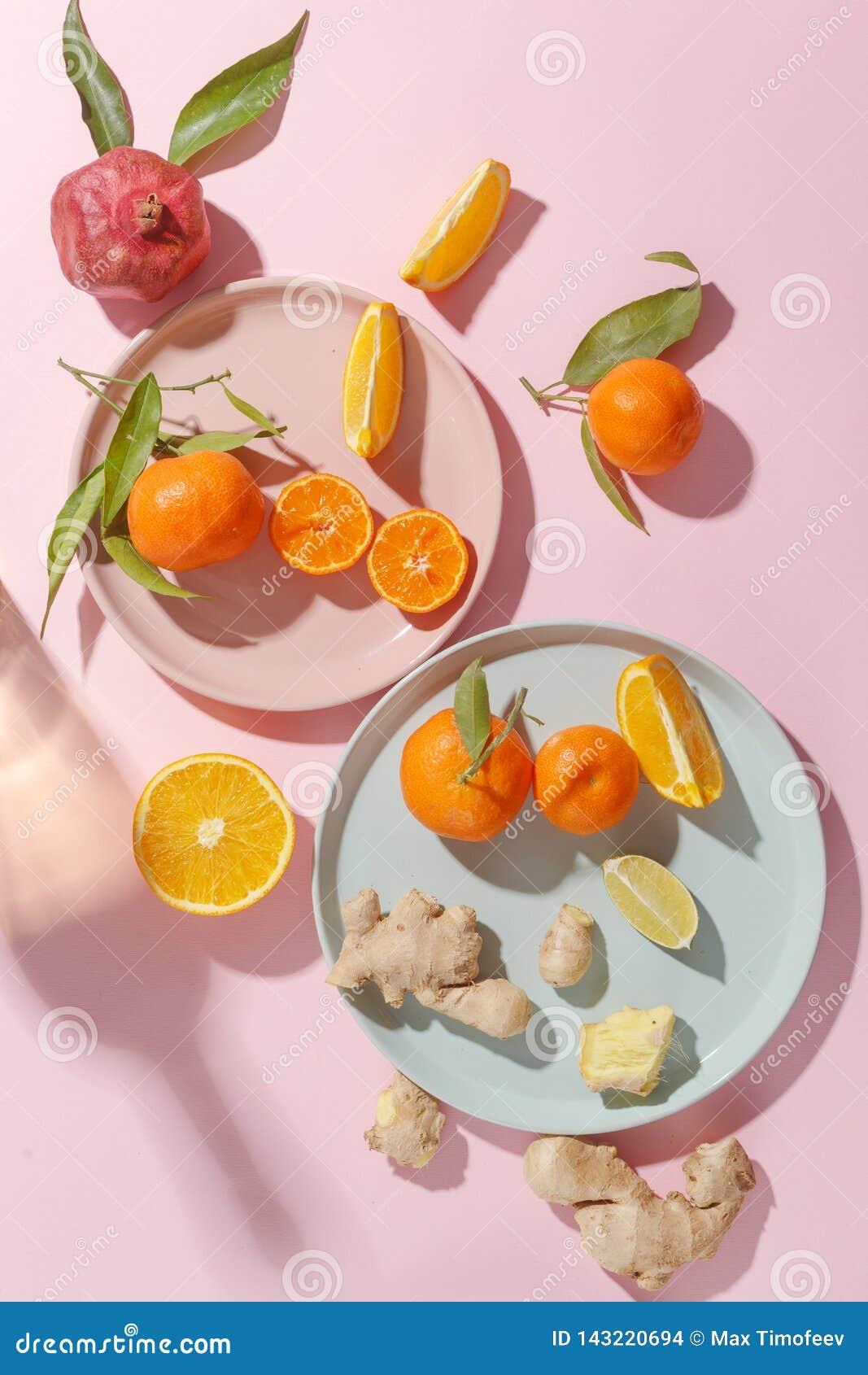 Verse sappige mandarijnen, granaatappels en gesneden vruchten op gekleurde platen op een roze achtergrond De zomerstemming, gezon
