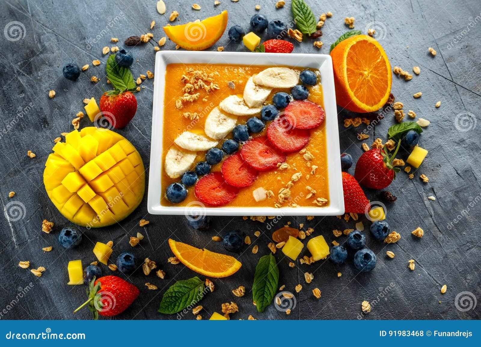 Verse Sinaasappel smoothie in kom voor ontbijt met bosbessen, granola, mango, aardbei en banaan