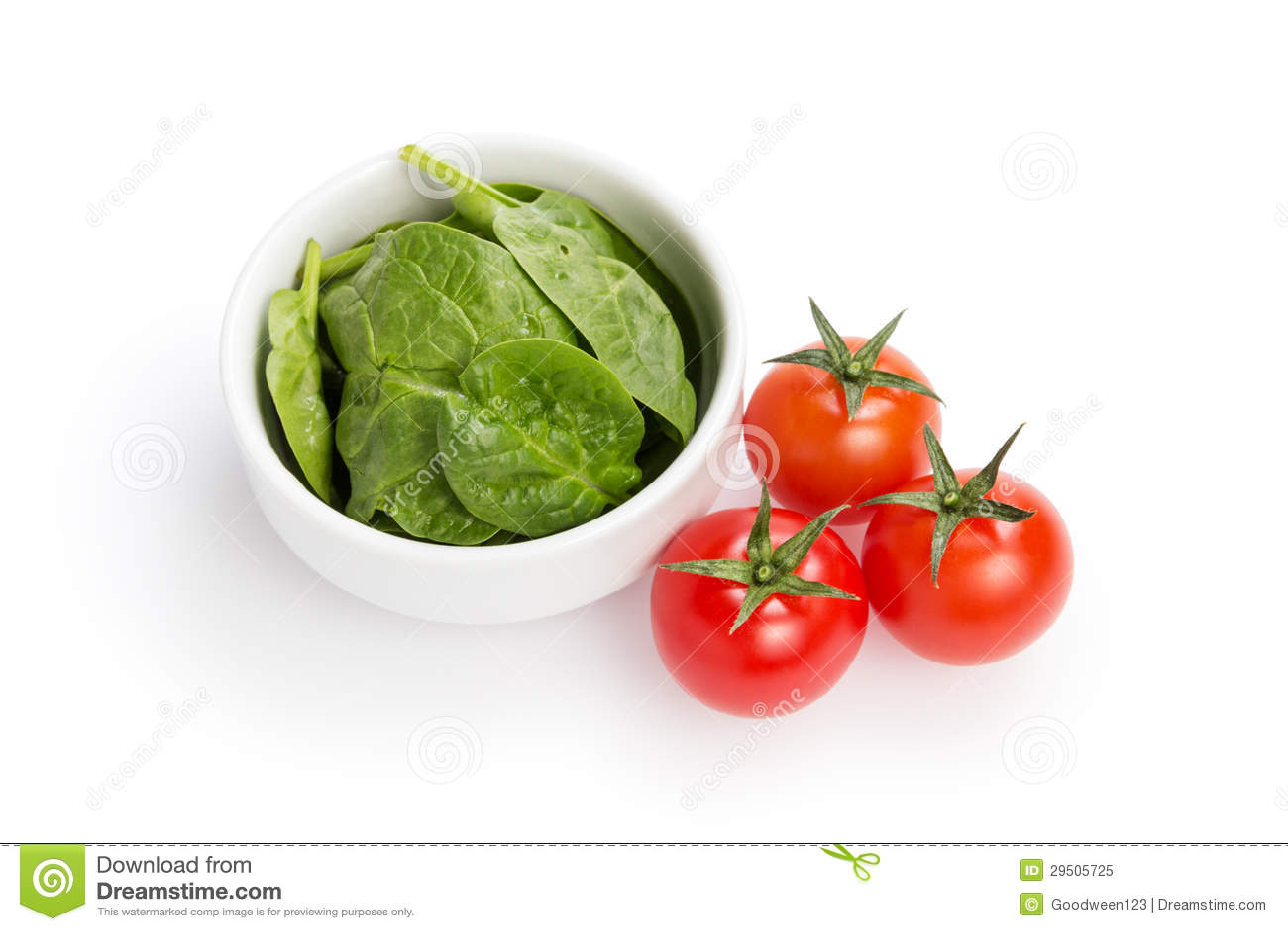 Verse spinaziebladeren in kom en tomaten
