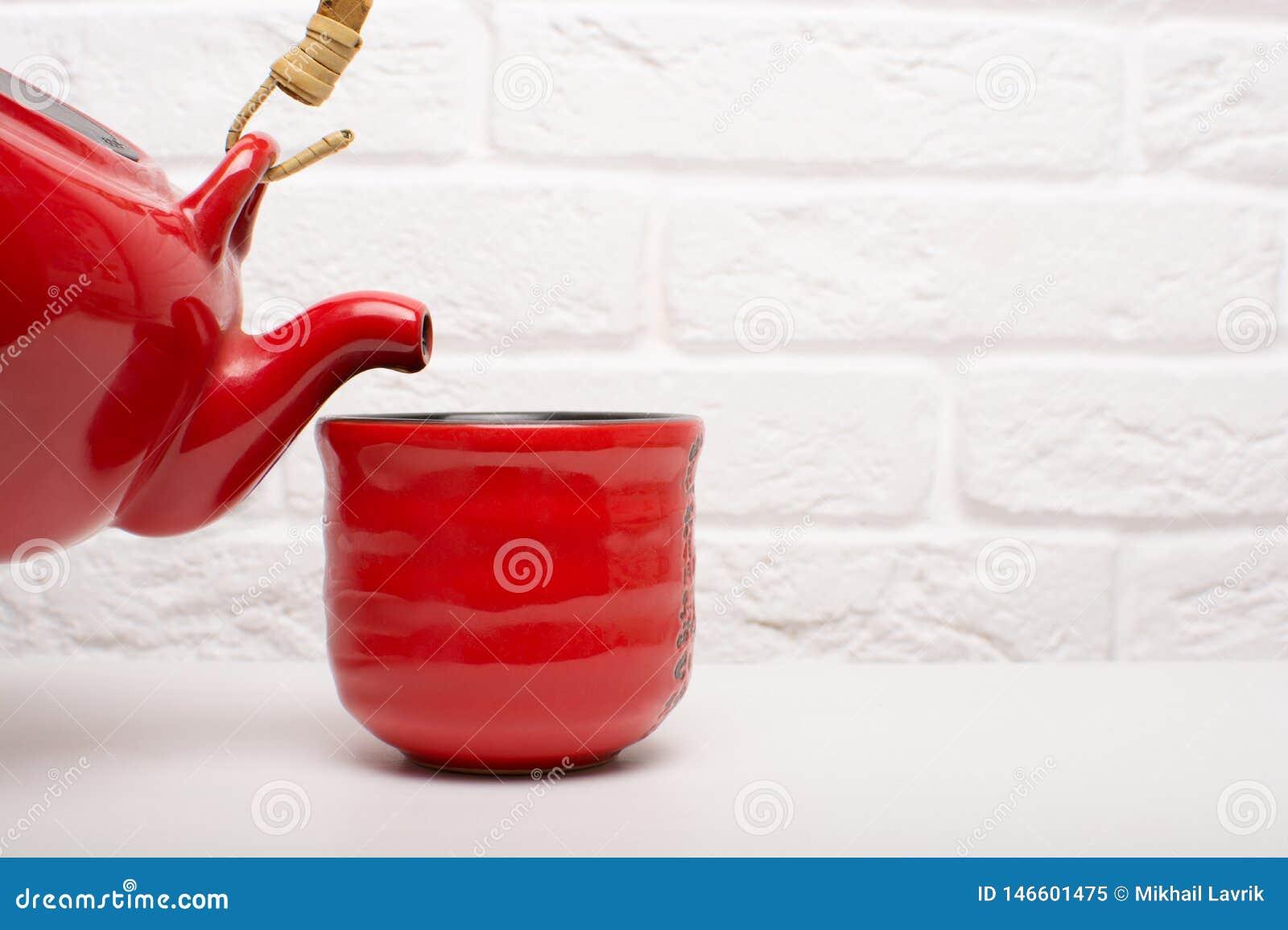 Versez le thé dans une tasse rouge
