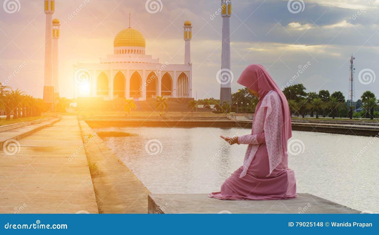 Versluierde Islamitische vrouw die een burka dragen die zich in een straal van luchtlicht in atmosferische duisternis bevinden
