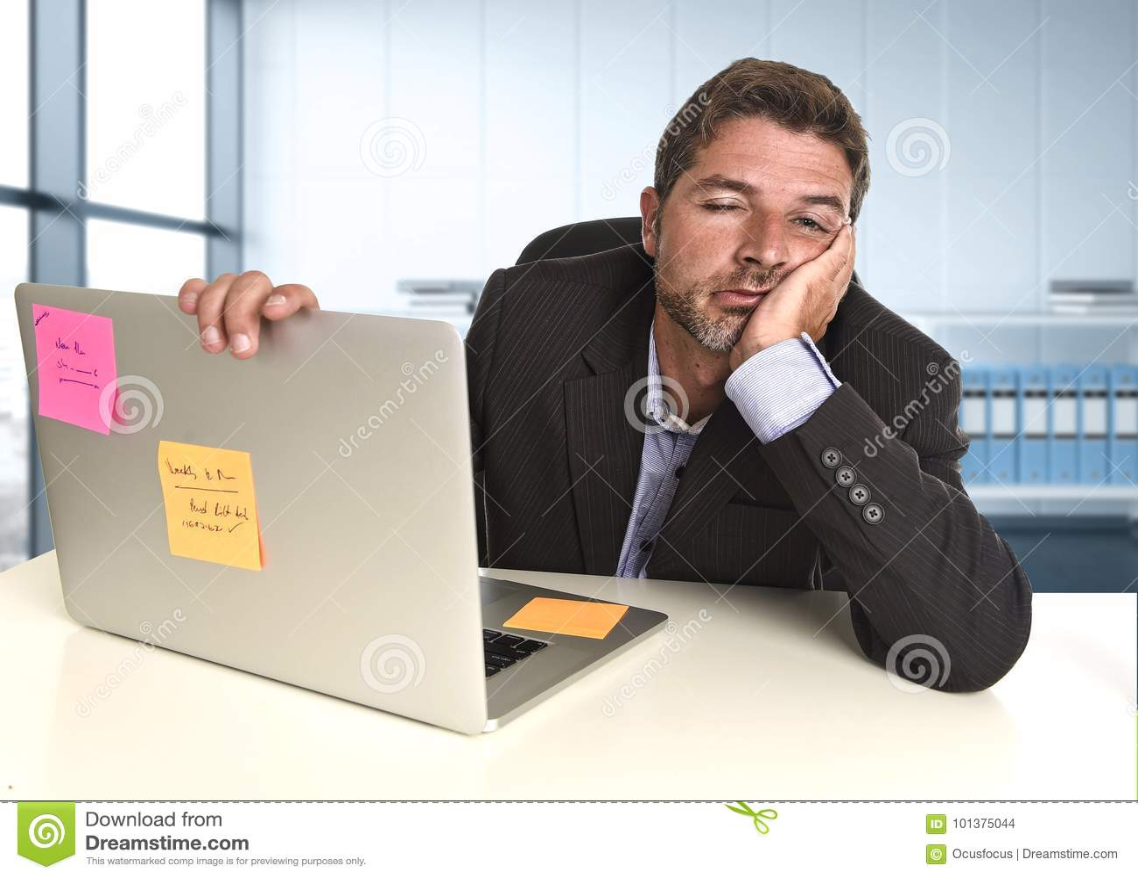Verspilde zakenman die in spanning bij bureaulaptop computer werken die uitgeput kijken
