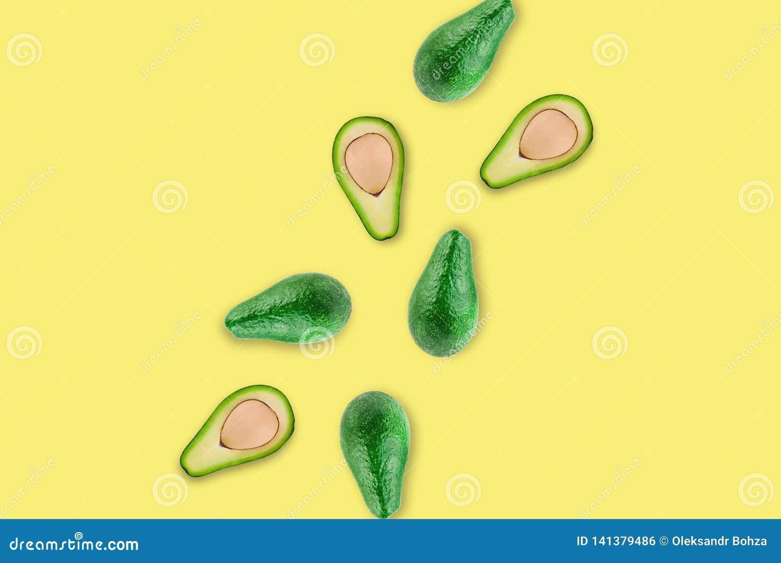 Verspreide verse wholes en de helften van organische avocado met pitten in centrum van gele lijst in keuken of markt