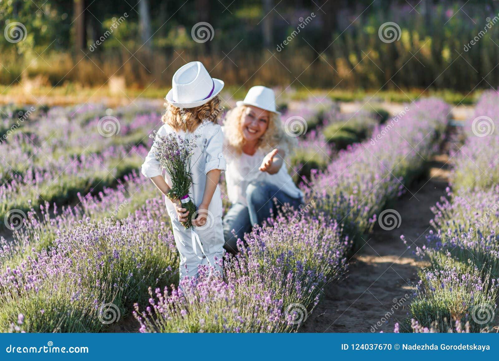 Versteckender Lavendel des Jungen hinter seinem zurück Kleiner Junge, der seiner Mutter einen Blumenstrauß von Blumen gibt Mutter