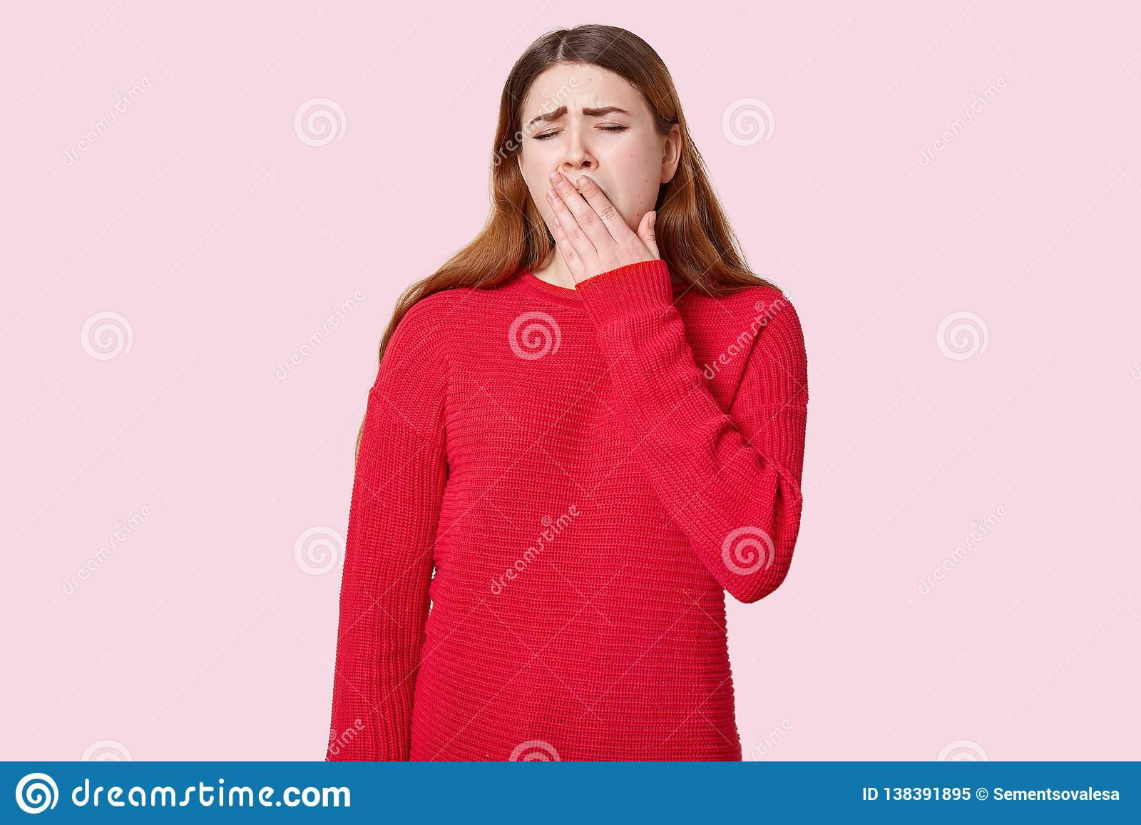 Verstoor slaperige vrouwengeeuwen en de dekkingsmond met palm, gekleed in rode uitrusting, stelt over rooskleurige studioachtergr