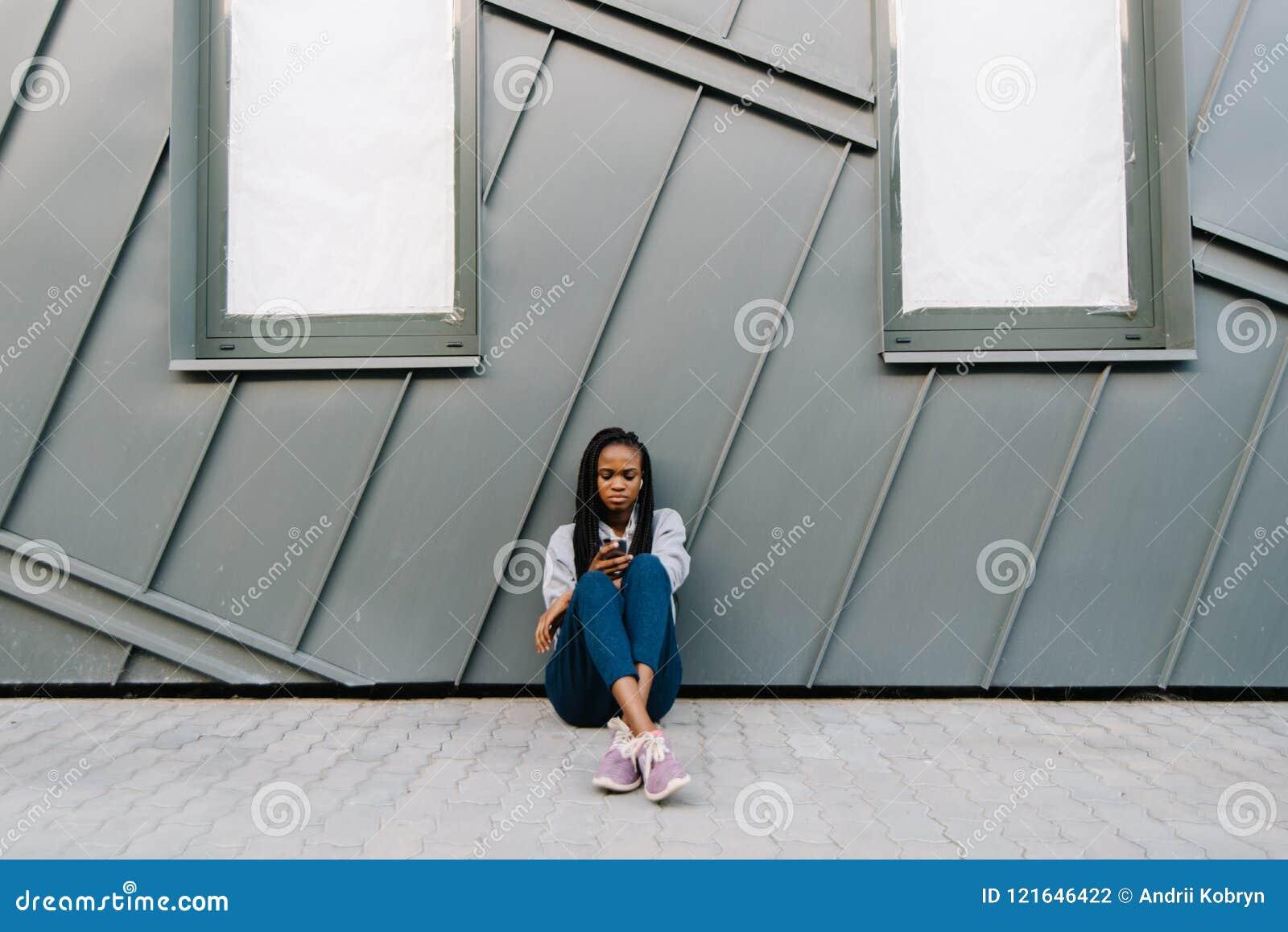 Verstoor zekere Afrikaanse vrouw texting en doorbladert o nt hij mobiele telefoon terwijl het zitten op de grond en het leunen