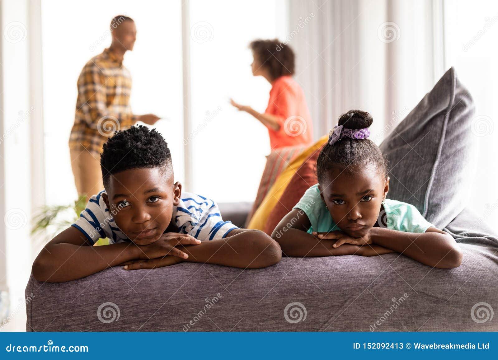 Verstoorde kinderen die op een bank zitten terwijl hun ouders die op de achtergrond debatteren