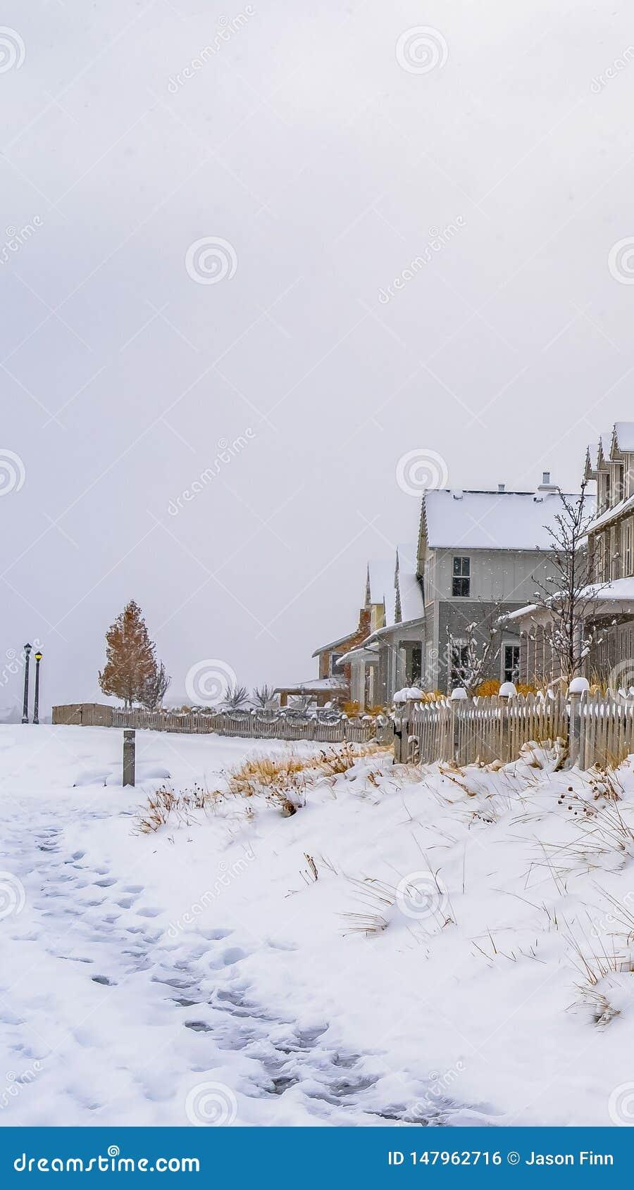 Verticaal die de Winterweer met sleep op de sneeuw naar de huizen in Dageraad wordt gestempeld
