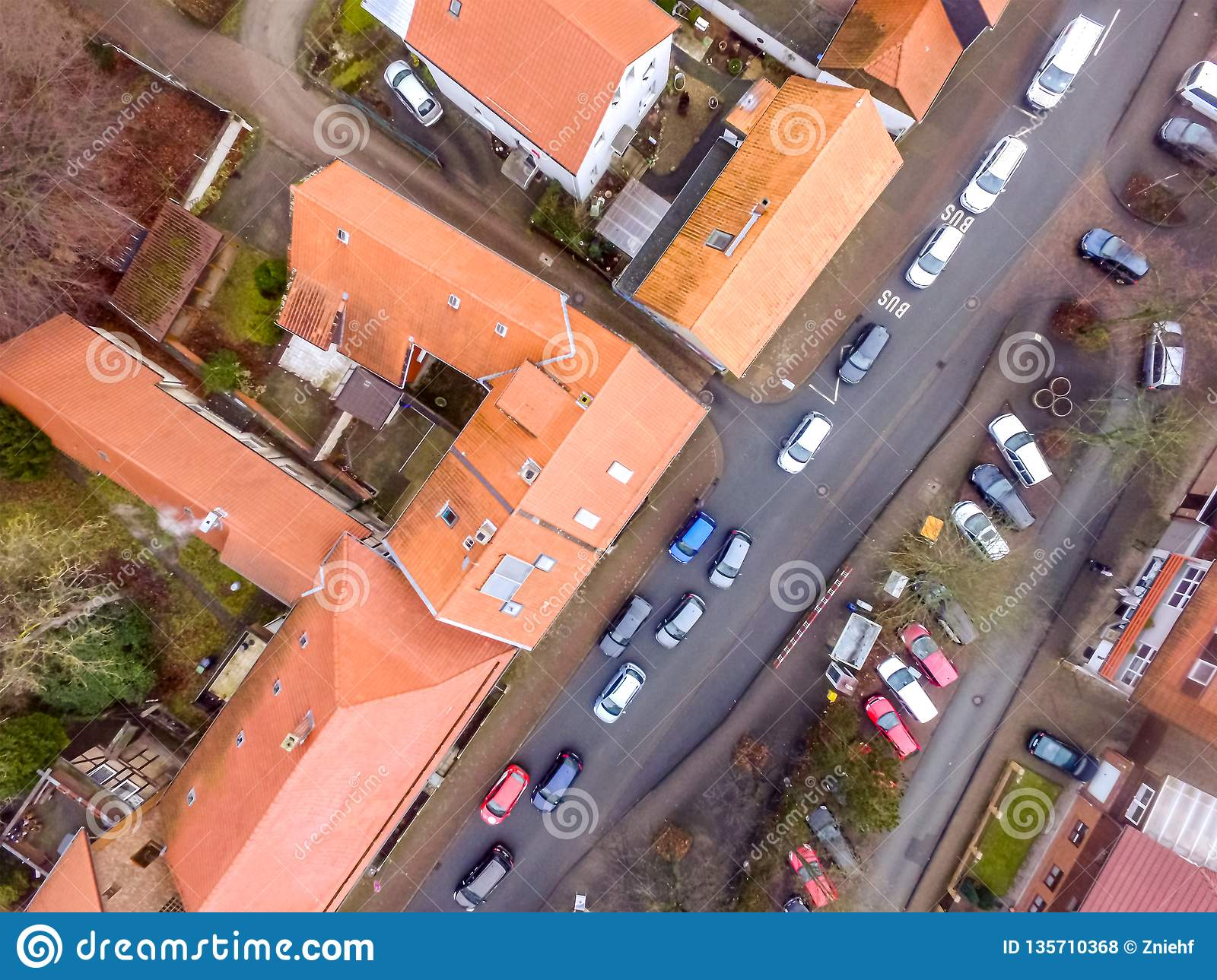 Vertical aerial photo of the main street in a suburb with terraced houses and many cars